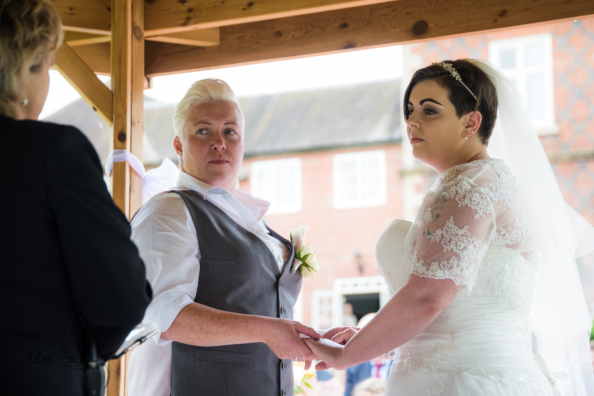 the bride and bride stand together saying their vows during their outdoor wedding ceremony