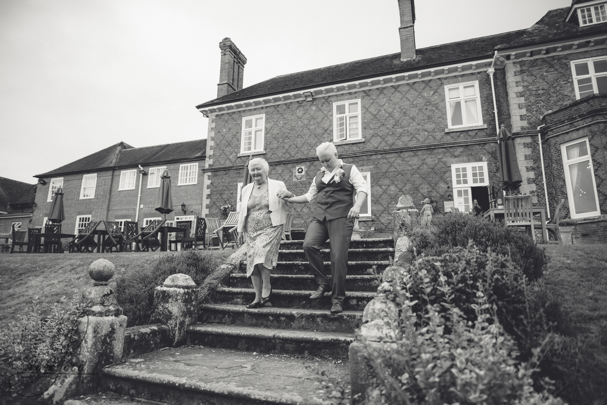 wedding guests walk down the steps of albrighton hall towards the gardens