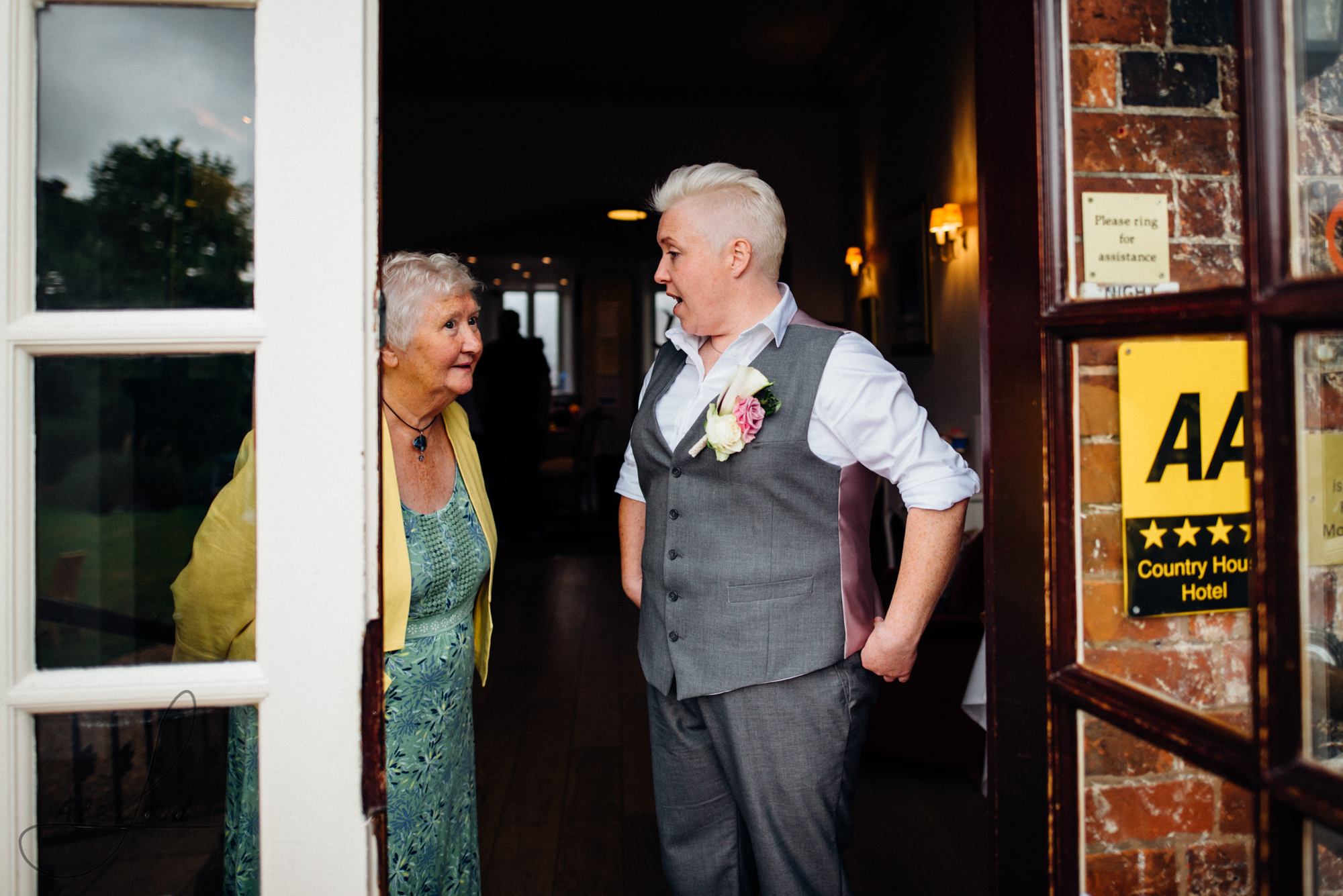 a bride stands in the doorway of her wedding venue chatting to one of the older guests