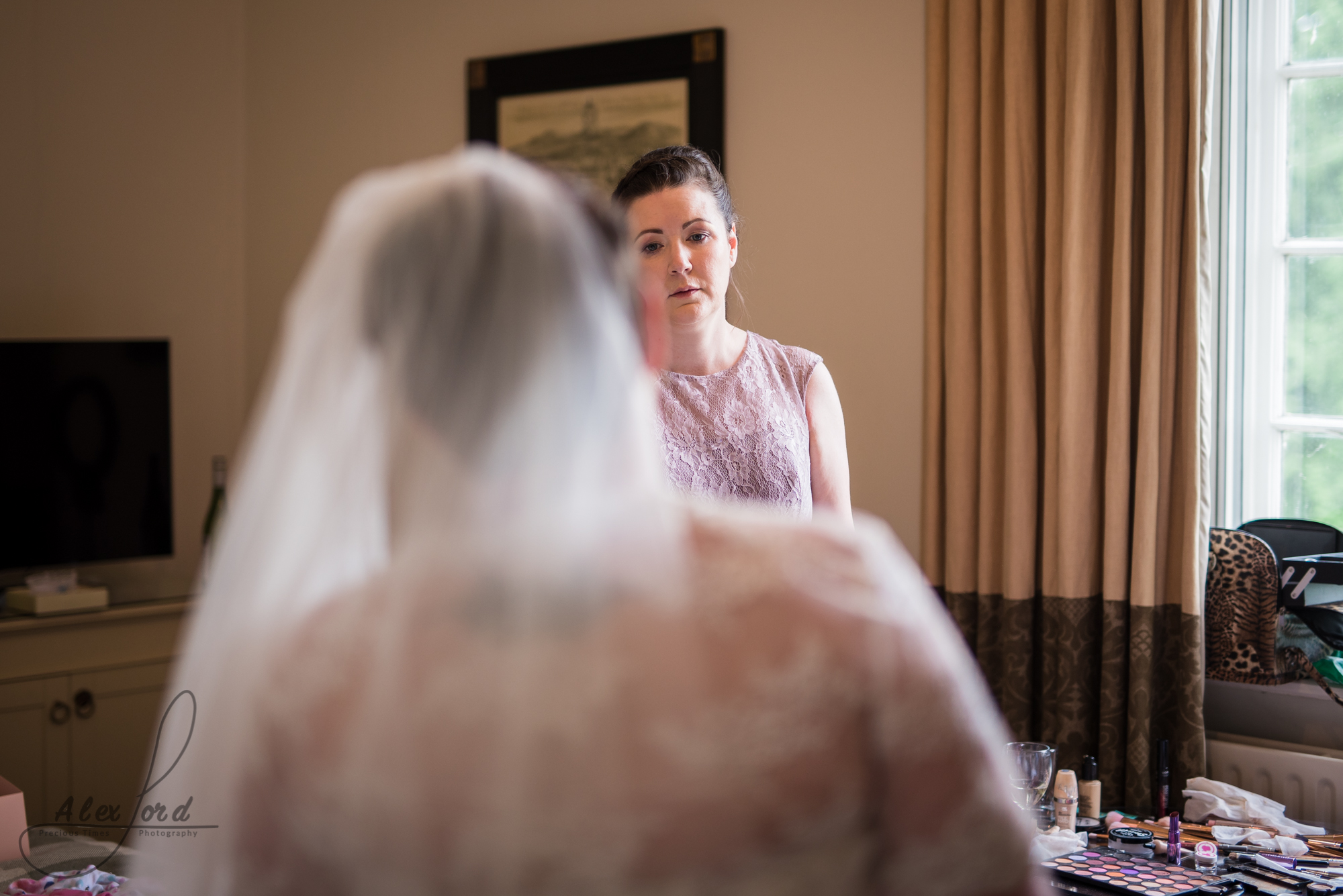 the back of the brides head as a bridesmaid looks at the bride