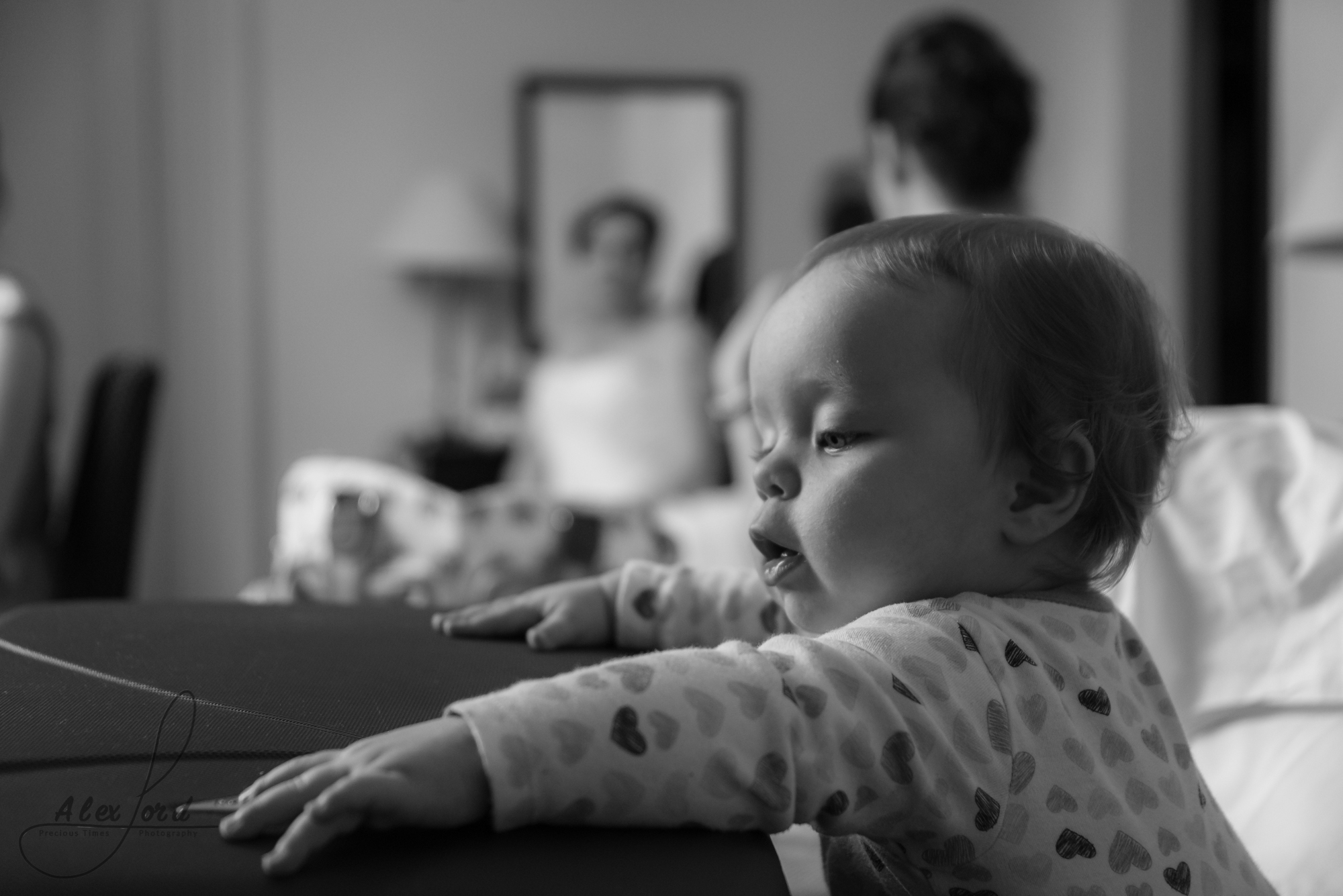 a young baby plays around while the bridesmaids getting ready in the background