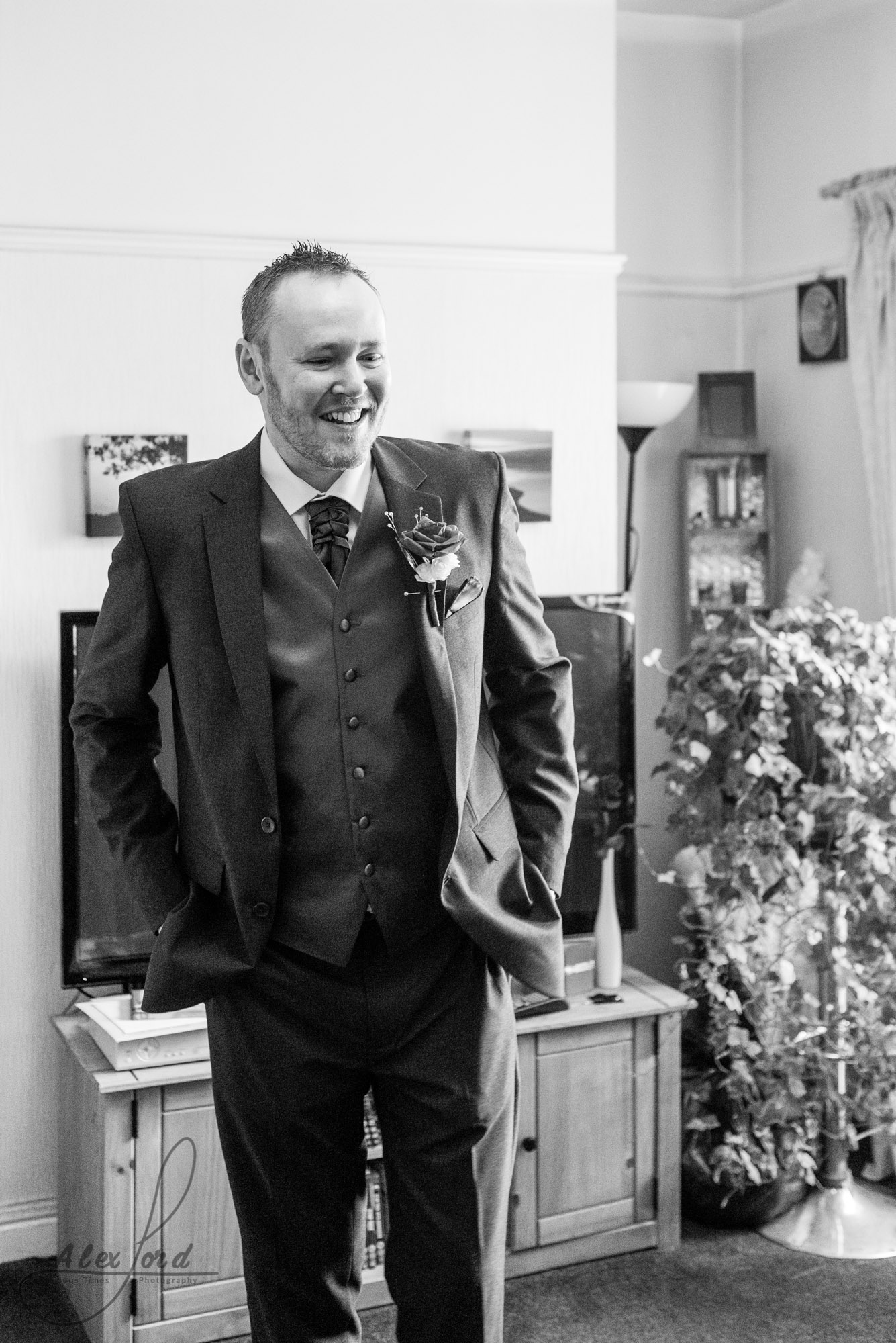 groom stands in his living room, dressed in his suit and wearing a rose, smiling widely