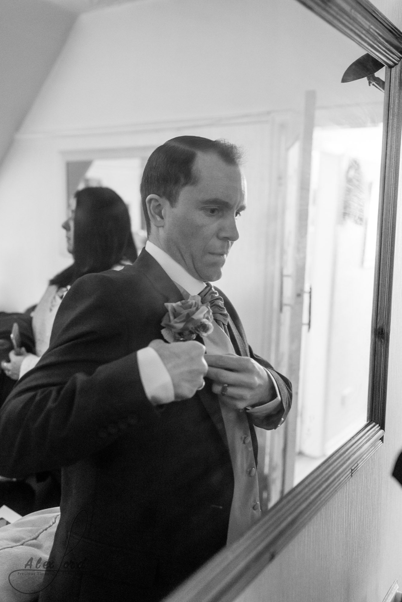 a member of the grooms party makes some final checks to his suit before they leave for the wedding ceremony