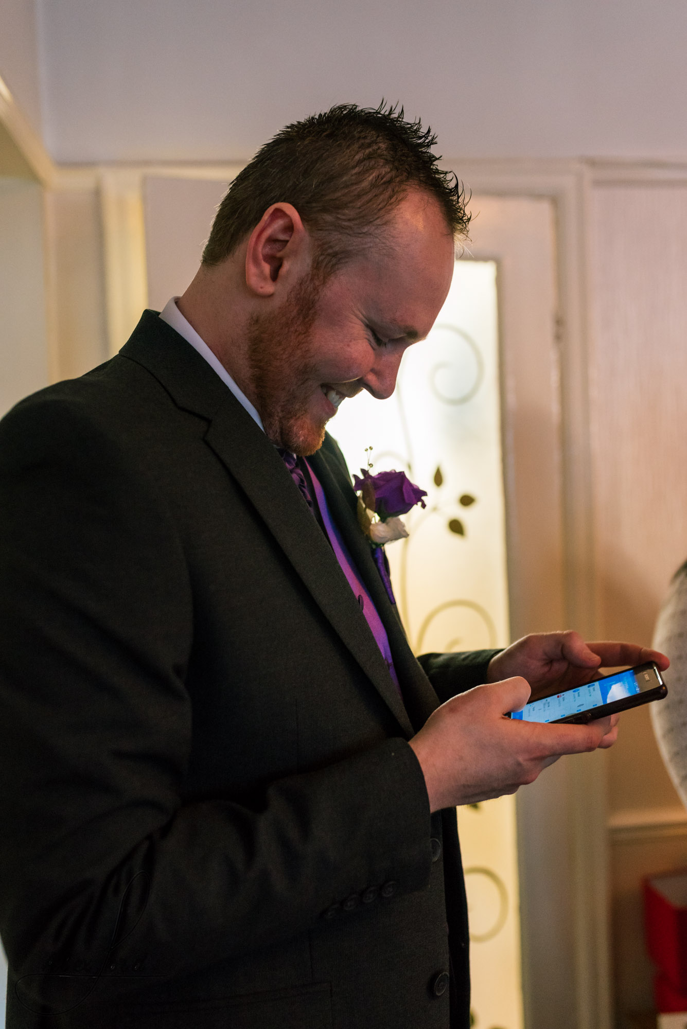 the groom checks his mobile phone before leaving for the ceremony