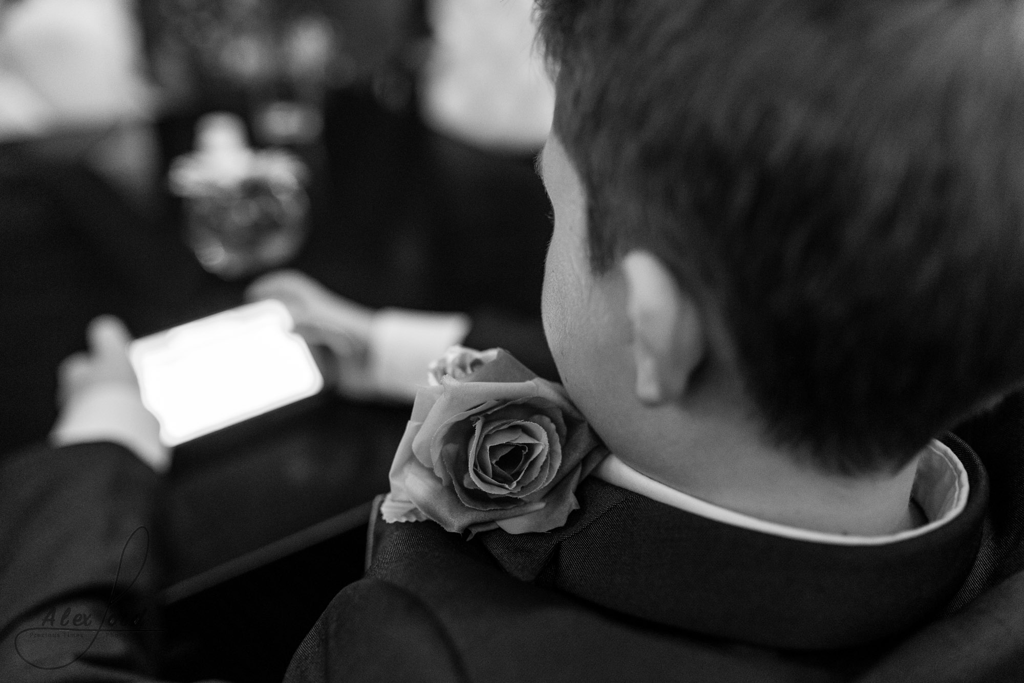 close up image of one of the young ushers playing on his phone before the wedding ceremony starts