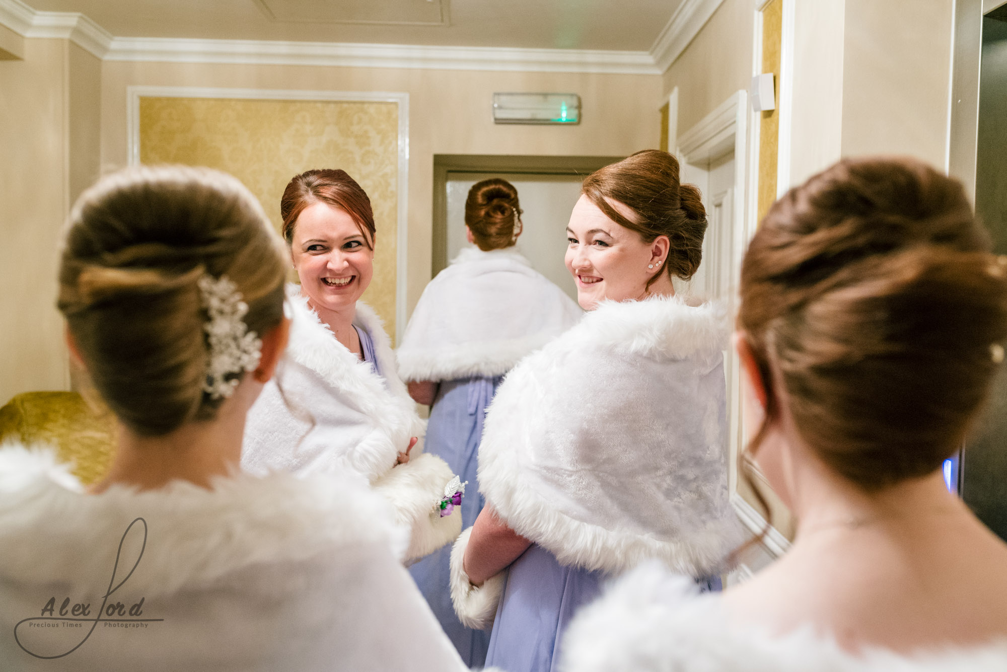 bridesmaids stand having a chat and a laugh together outside the ceremony room