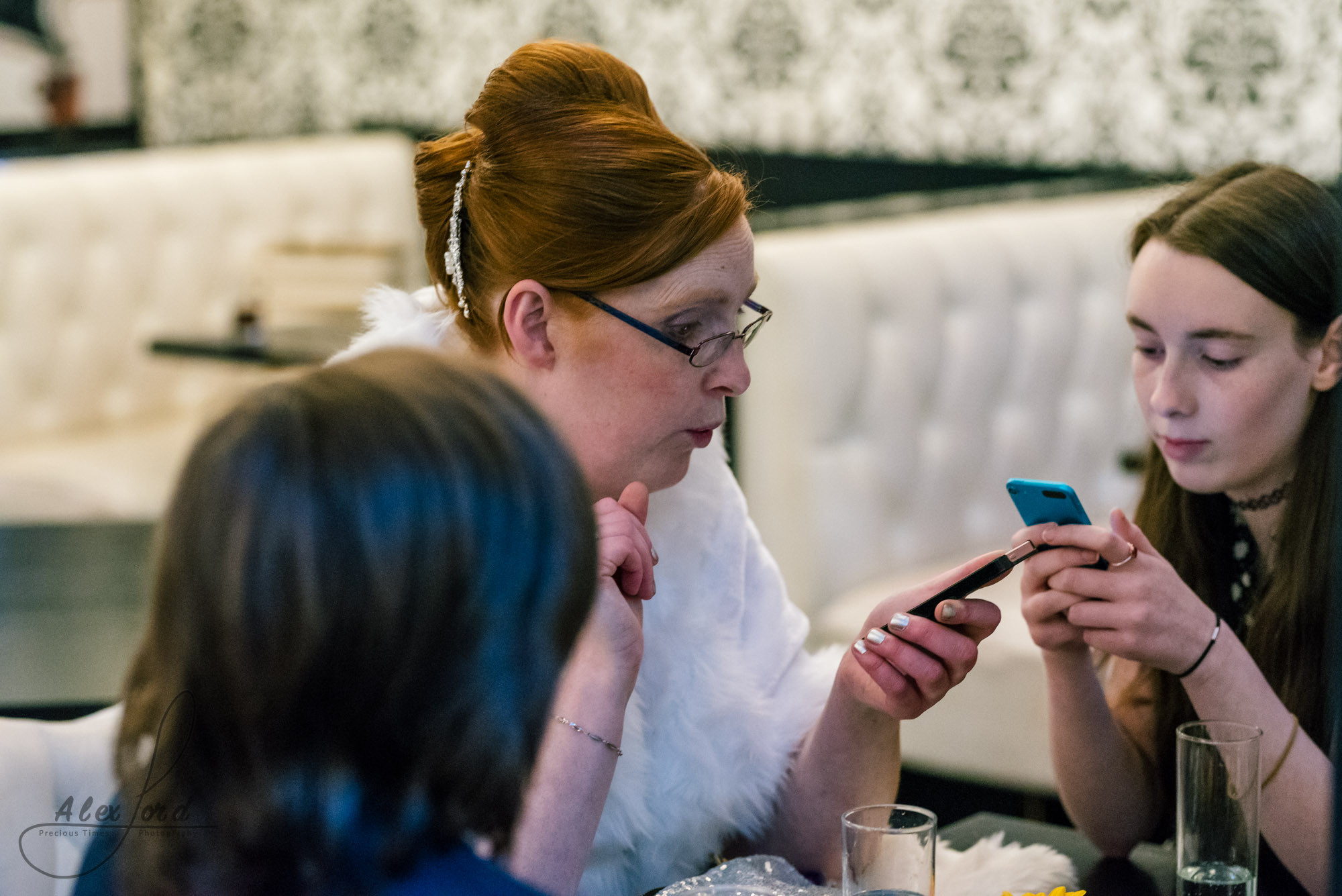 family members sit at a table during the reception and play on their phones