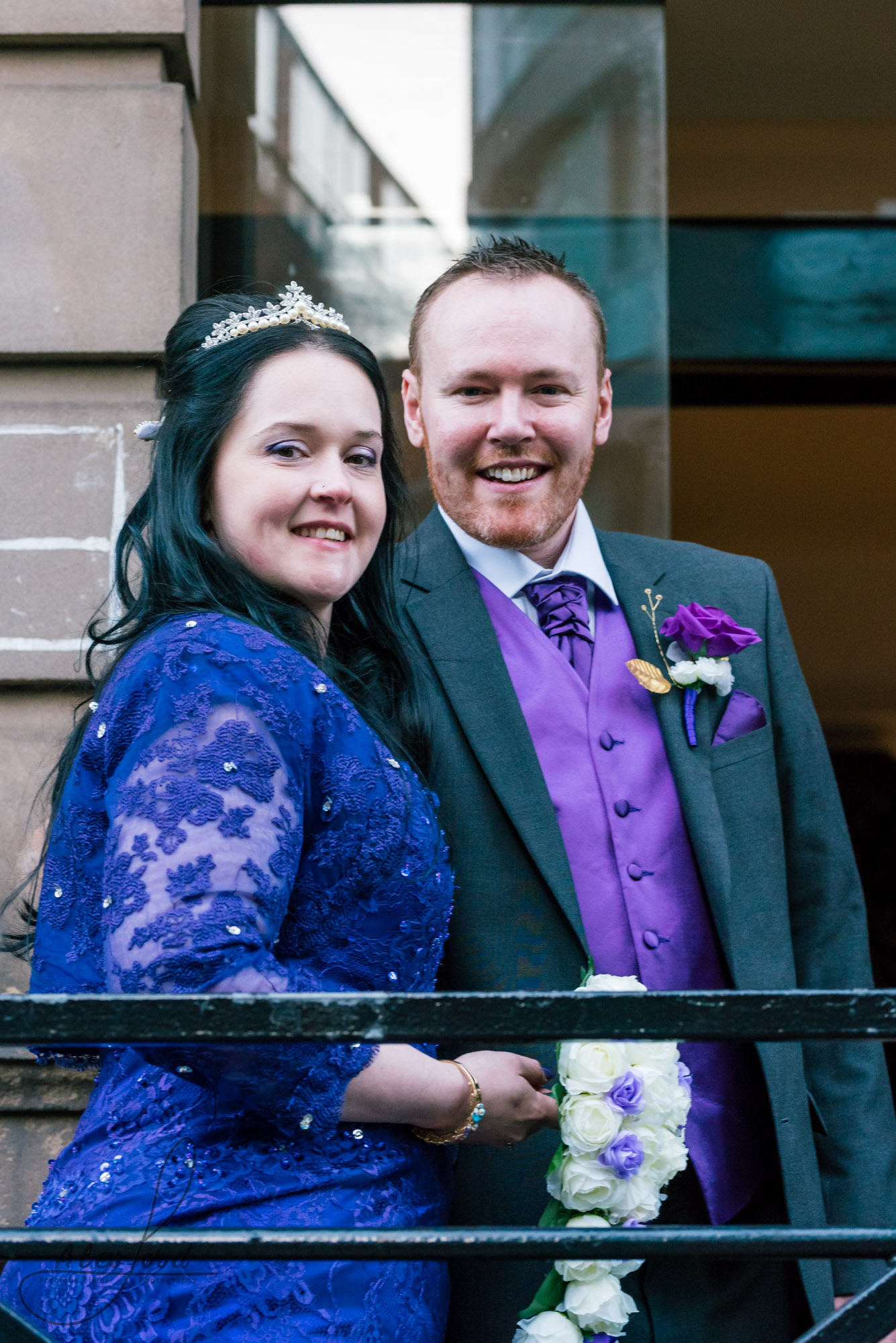bride dressed in a purple dress and the groom in a dark grey suit stand outside their wedding venue