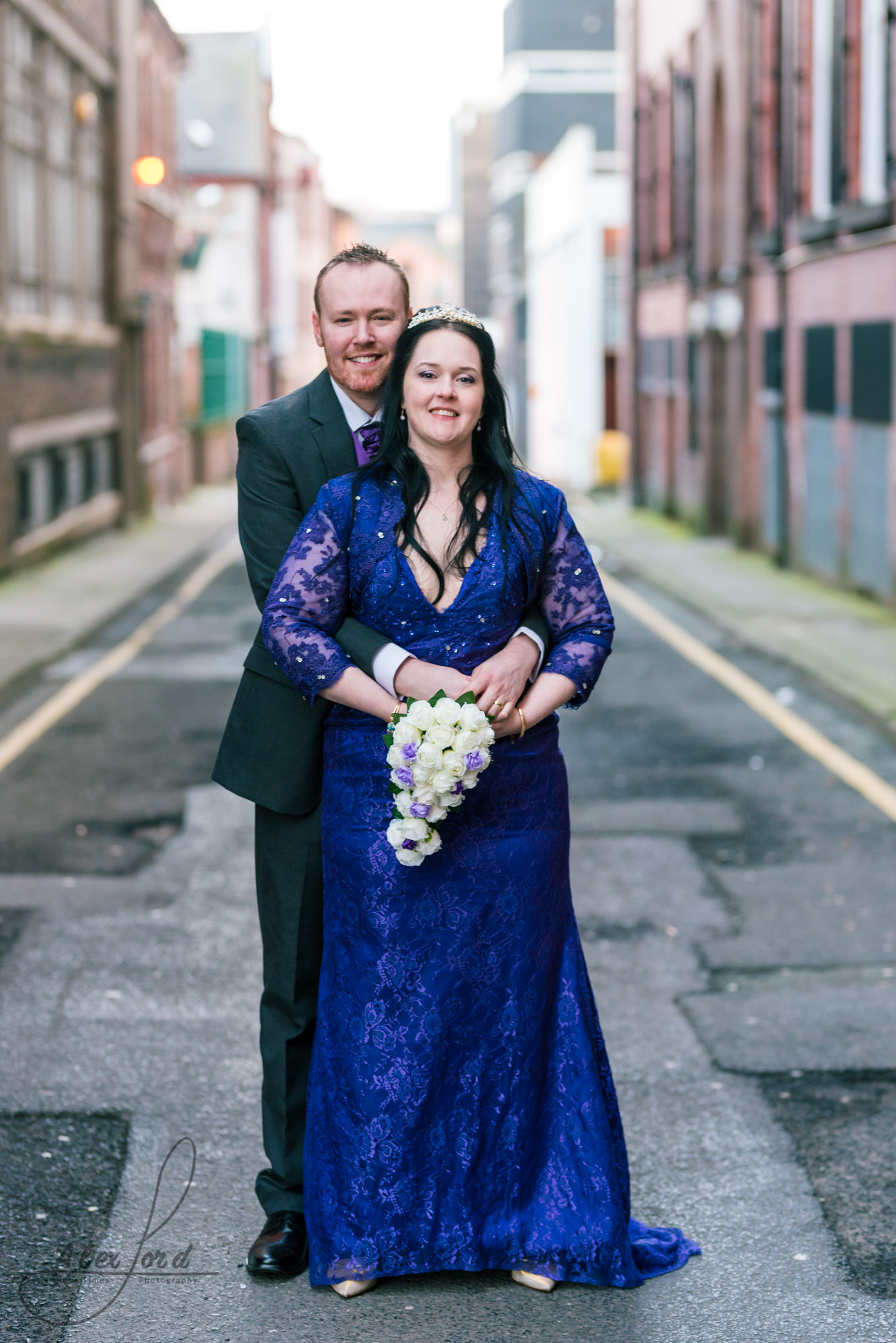 the bride and groom stand on a back street behind their liverpool wedding venue