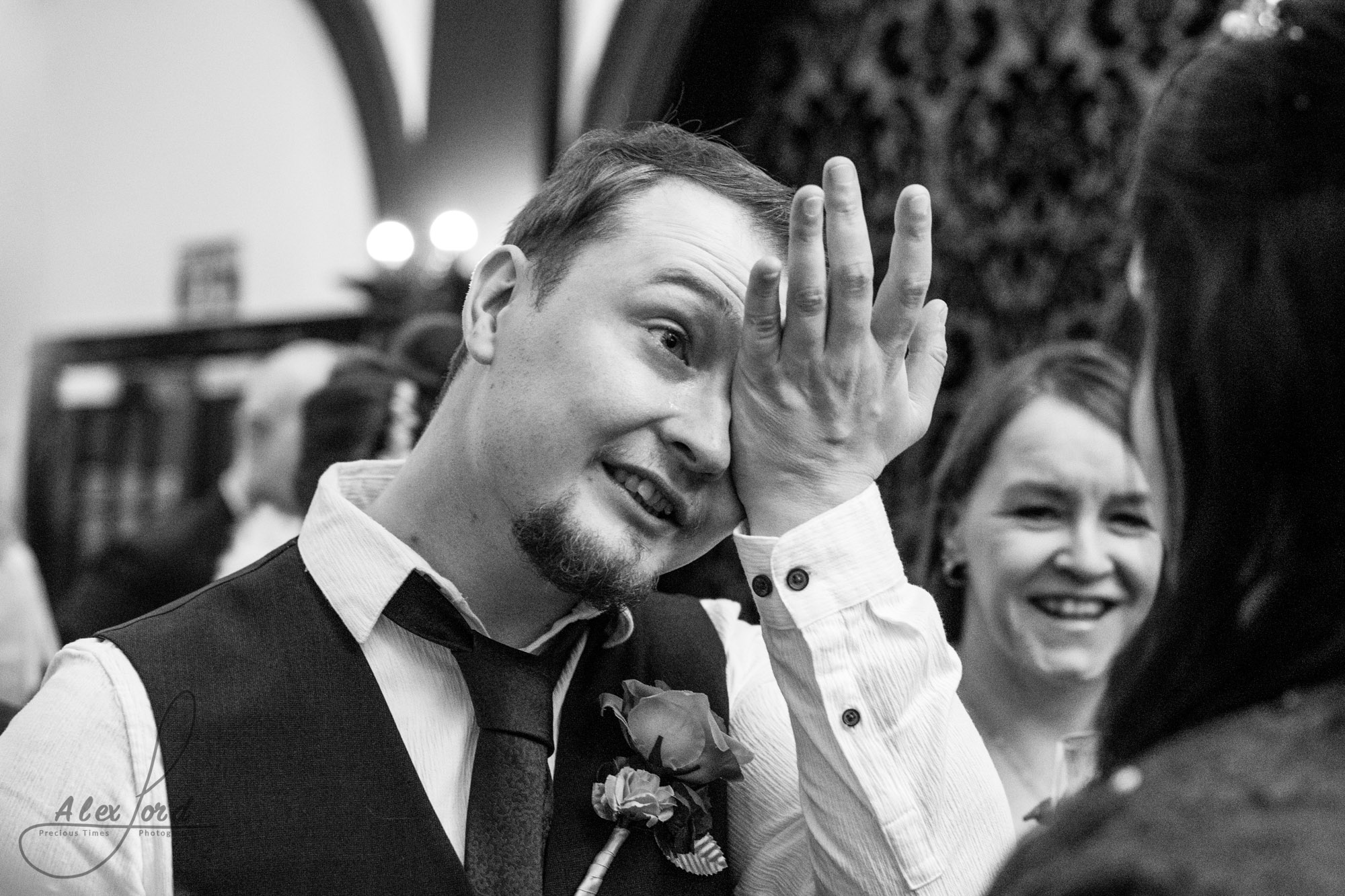 a male wedding guest puts his hand to his face to wipe away tears