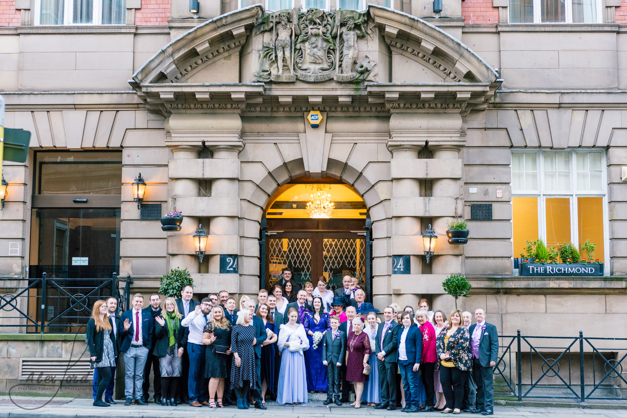 all the wedding guests gather together on the steps of the richmond hotel for a full family photo