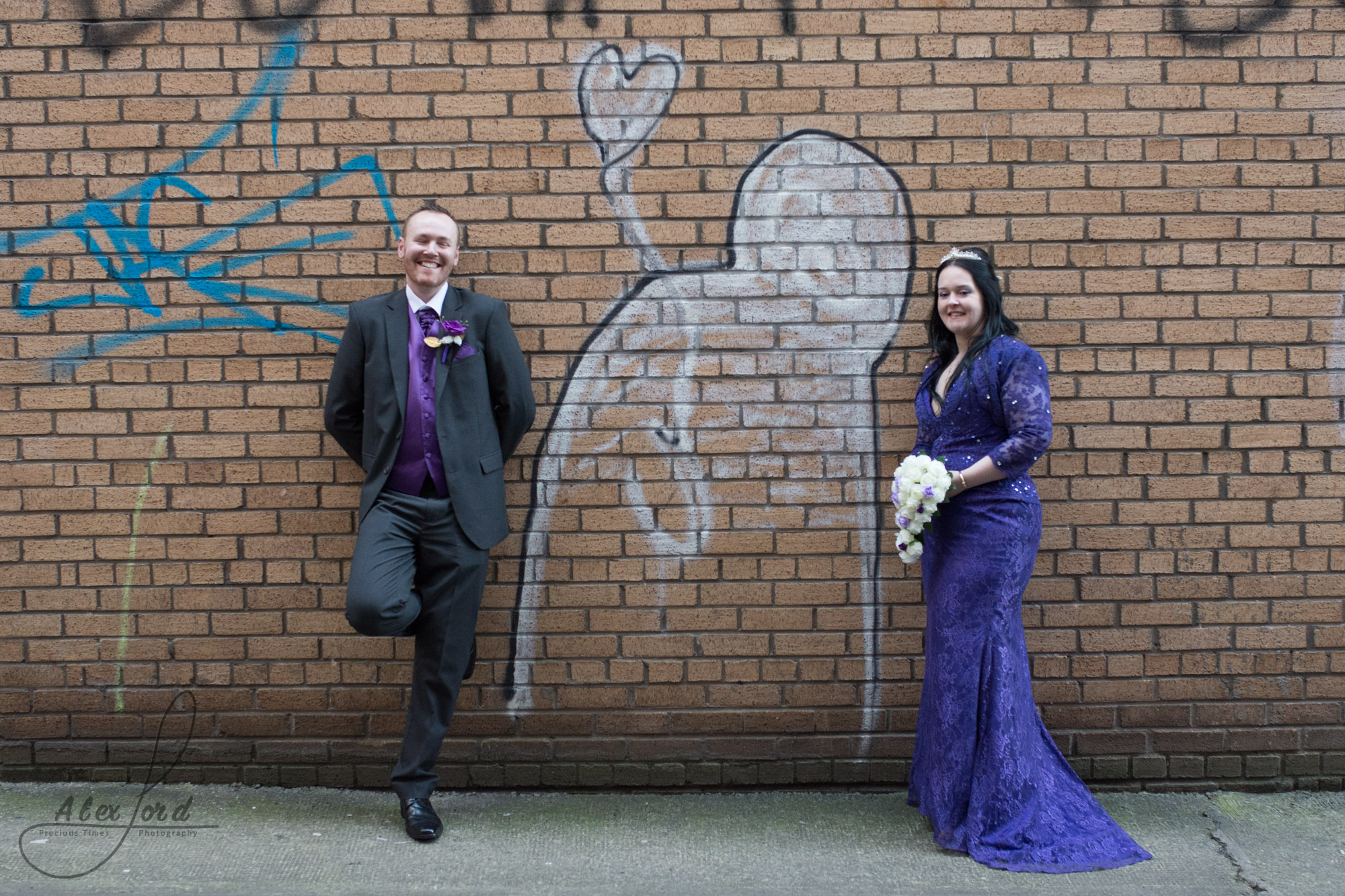 the bride and groom, bride dressed in a purple dress, pose against a red brick wall for their wedding photography