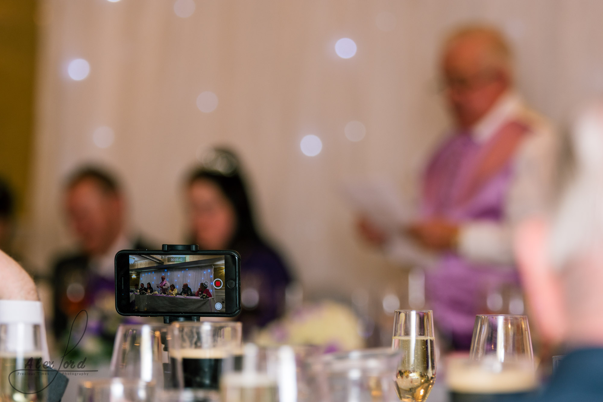 a wedding guest takes a photo of the brides father giving his speech