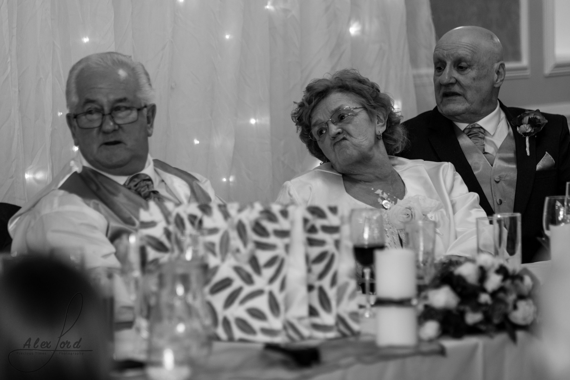 members of the brides family sit on the top table and listen to the wedding speeches