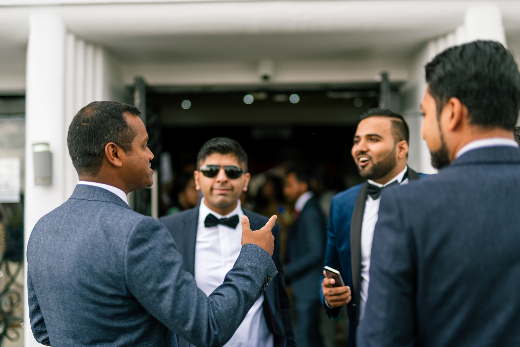 Four men waiting outside a Birmingham wedding venue for an Indian wedding