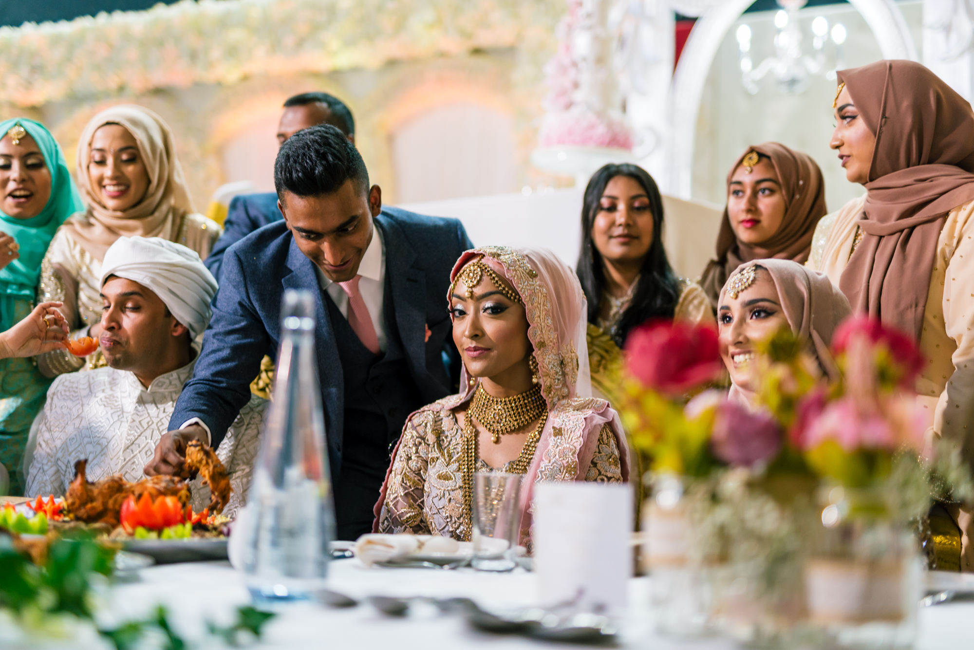 the bride and groom and their family gather round a large table full of indian wedding food