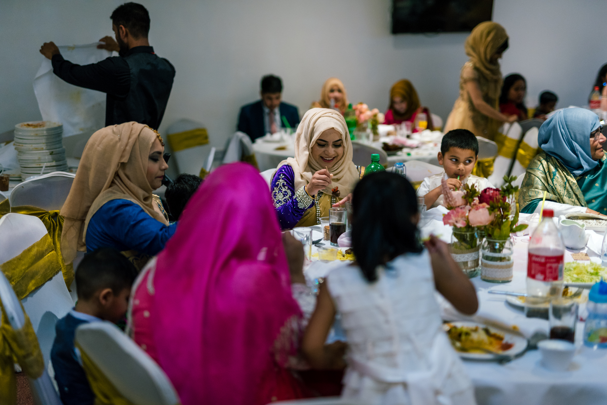 wedding guests sit round a table eating indian wedding food