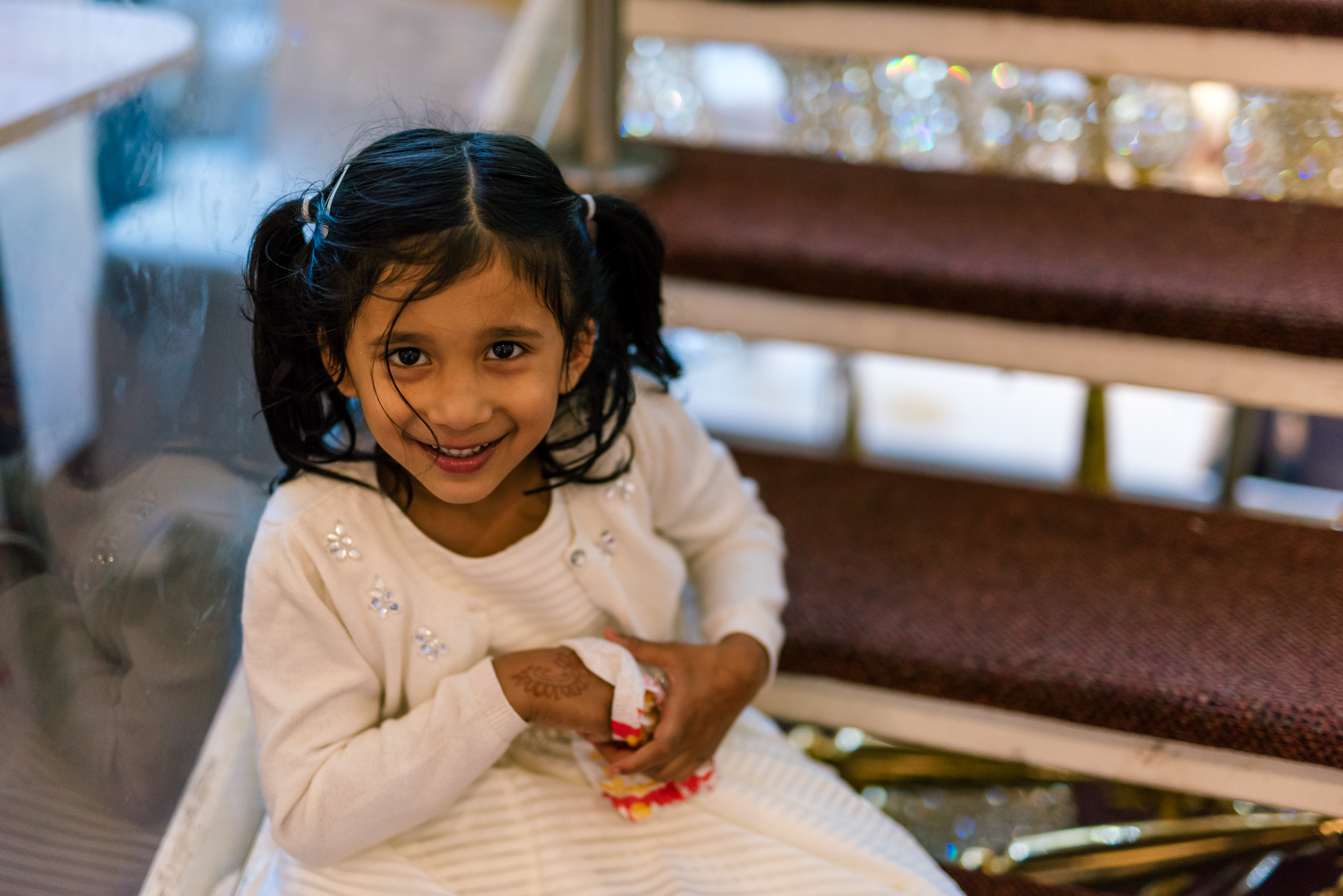 a young girl wedding guest smiles at the camera