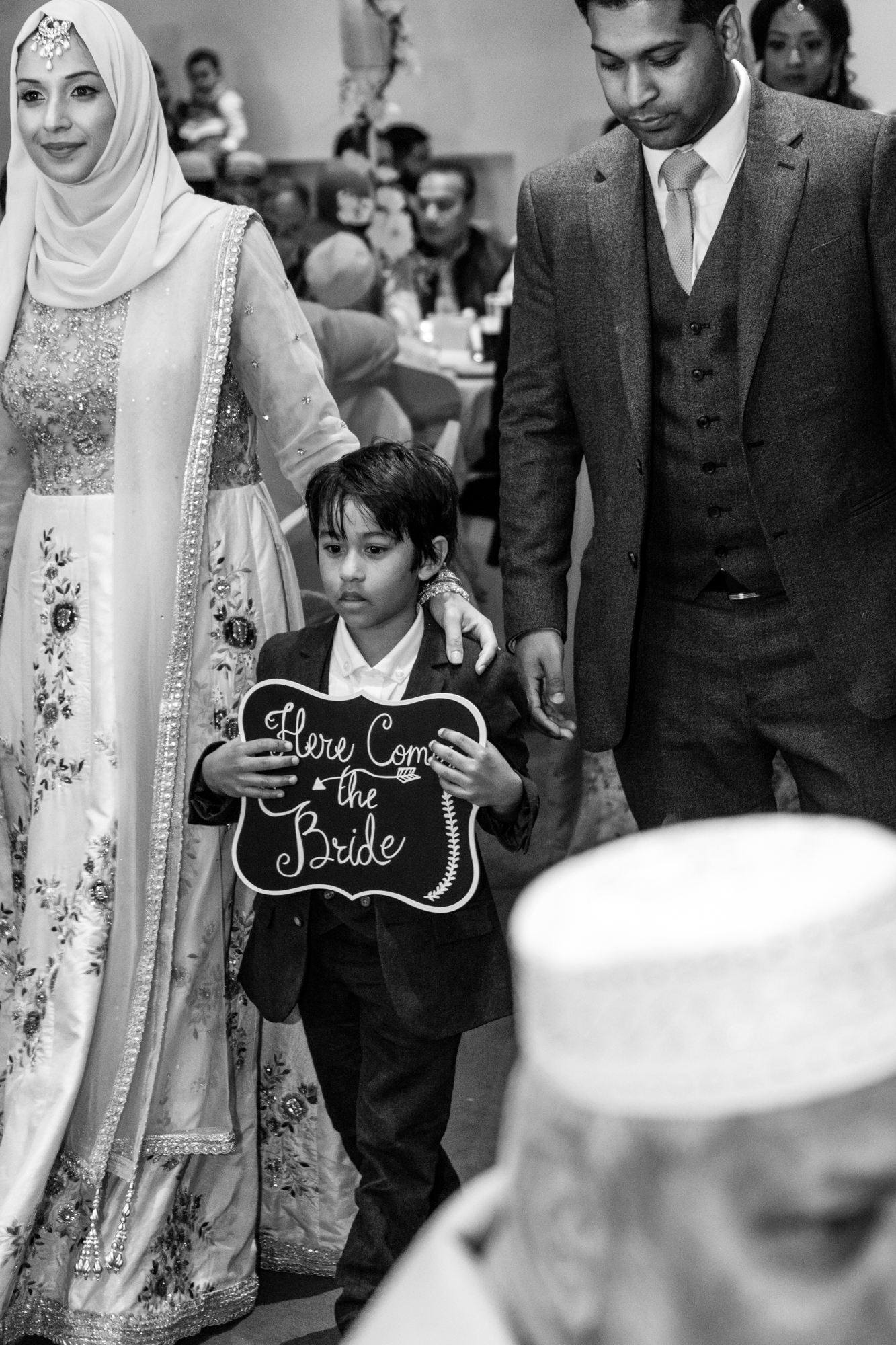 a young boy escorts the bride up the aisle with a blackboard in his hands