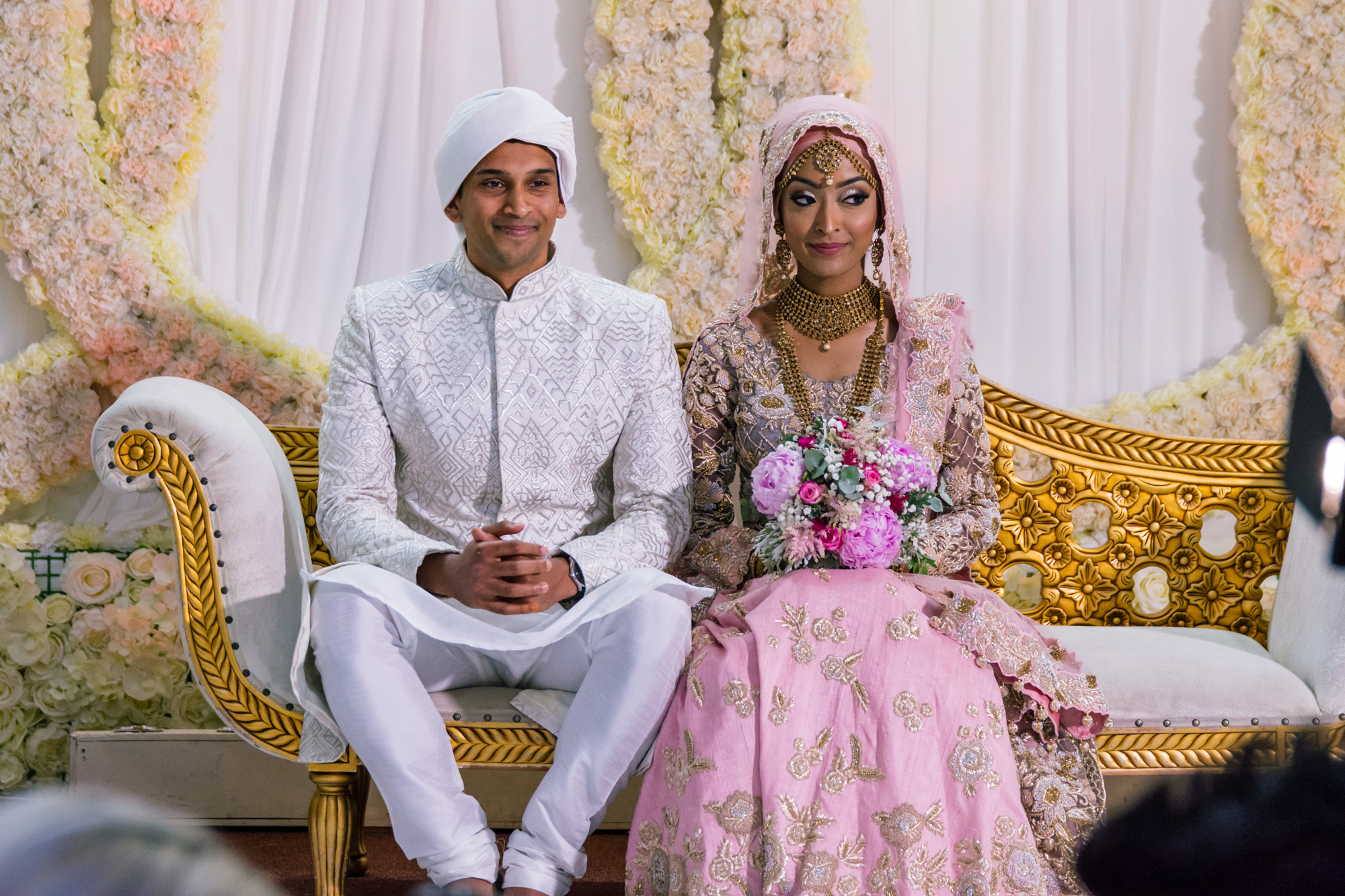 the bride and groom sit together on a double chair on the stage of the wedding venue. The groom wears traditional indian wedding clothes, in pure white. The bride is in pink and gold