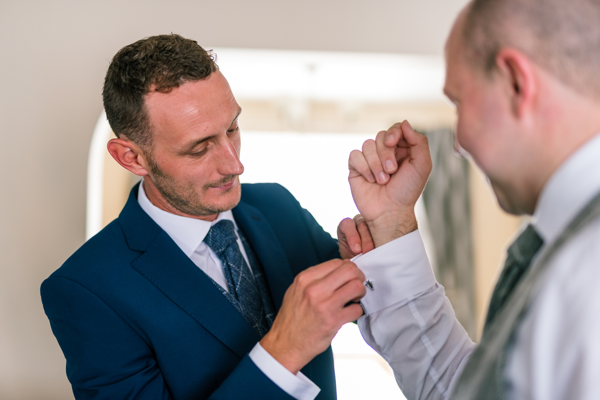 groom sorts his cufflinks