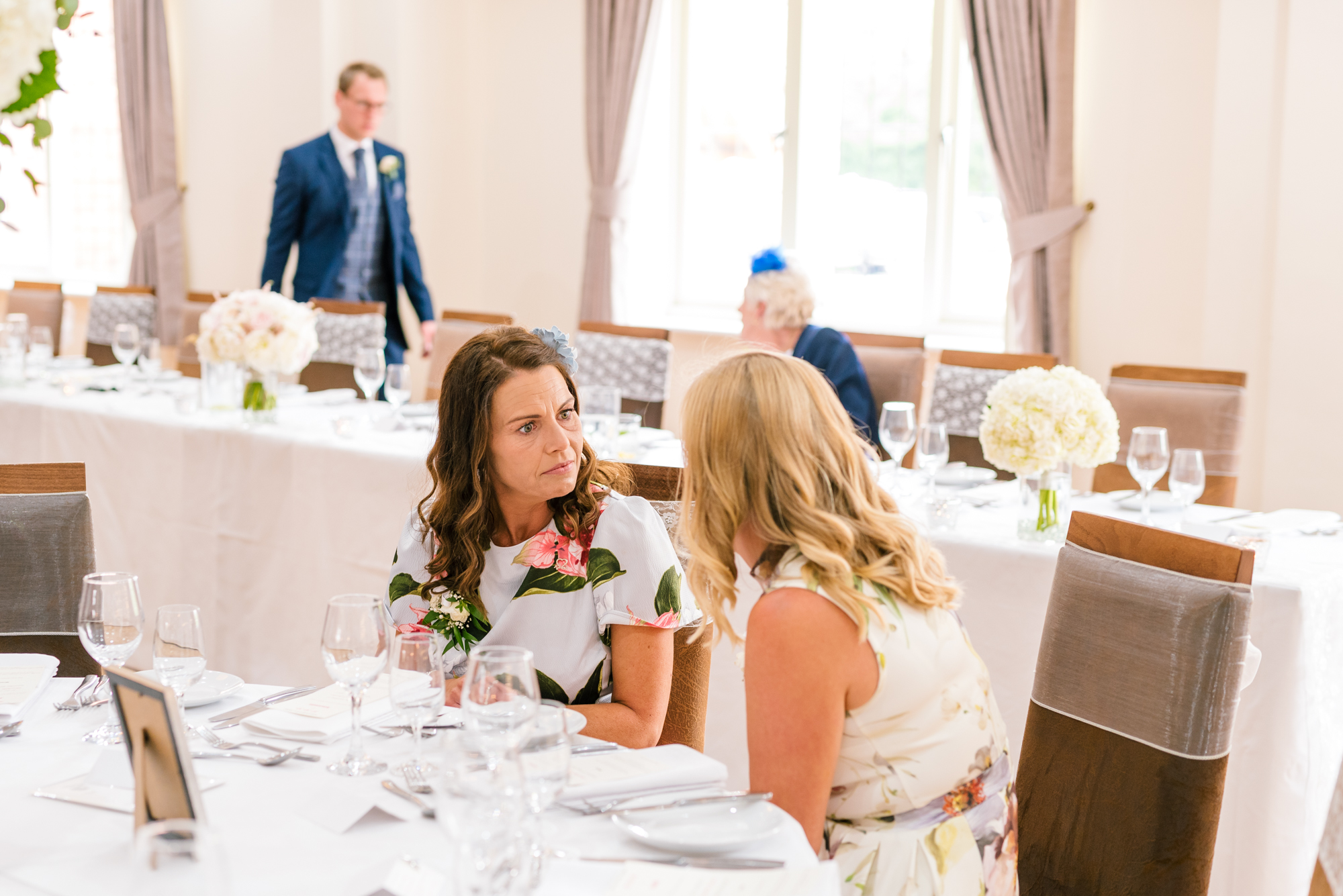 two wedding guests having a chat at a table