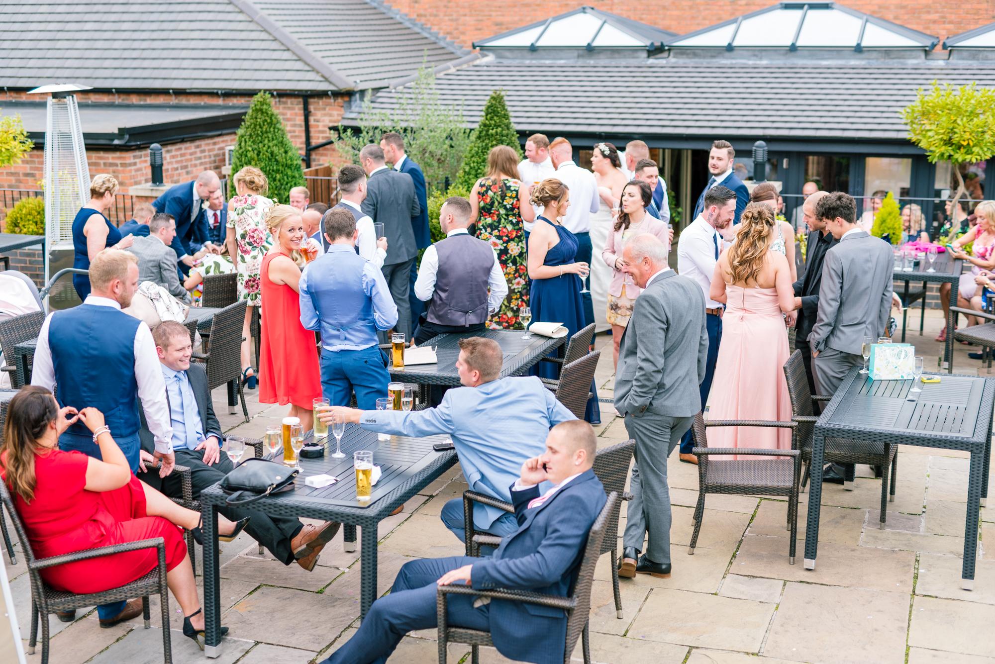 wedding guests outside enjoying a summer evening