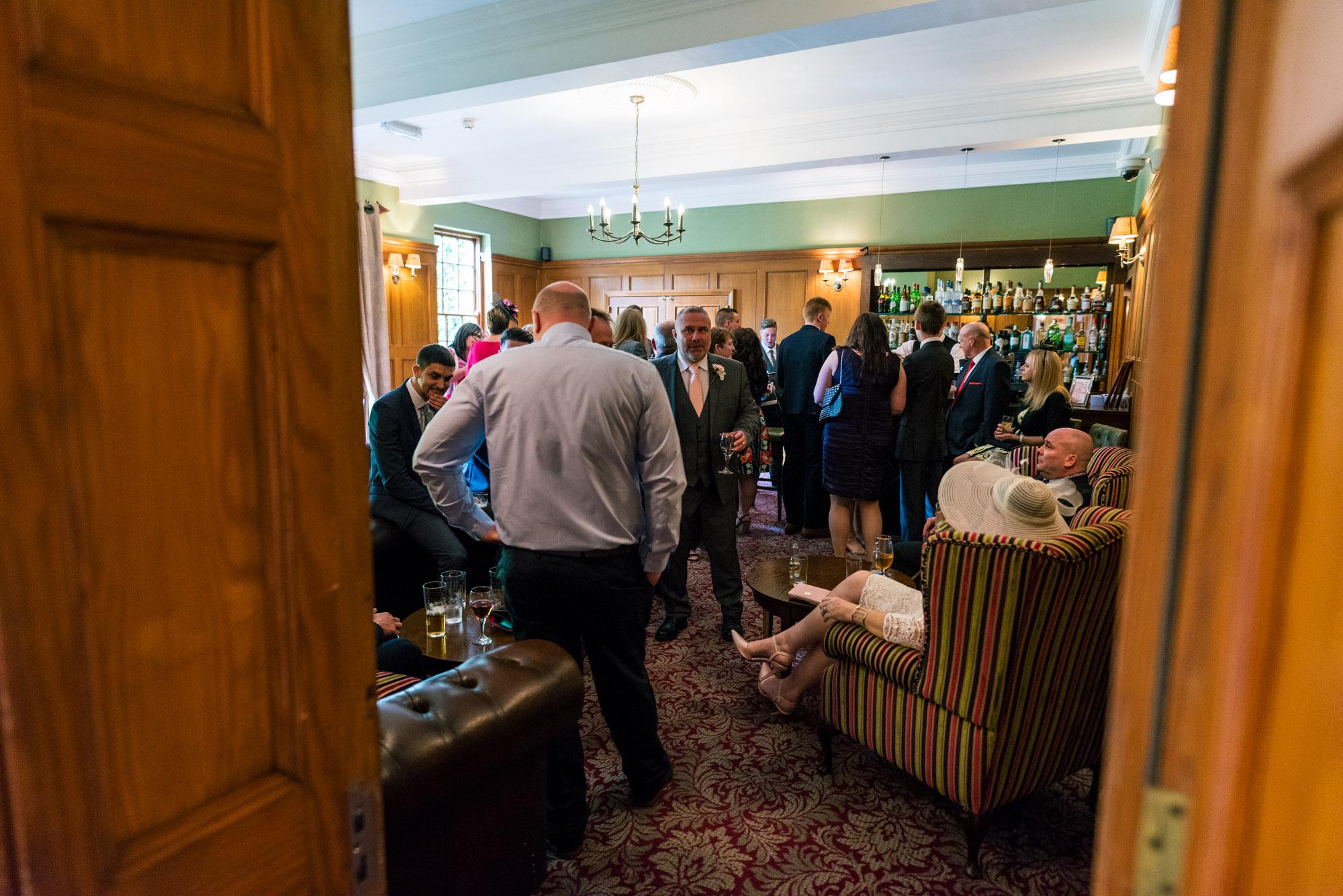 Wedding guests at the bar at Nunsmere Hall