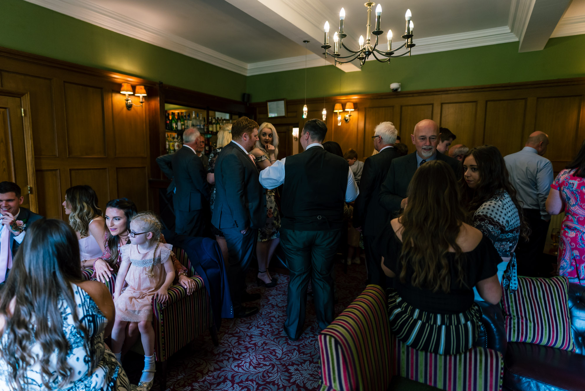 Wedding guests gather in the bar