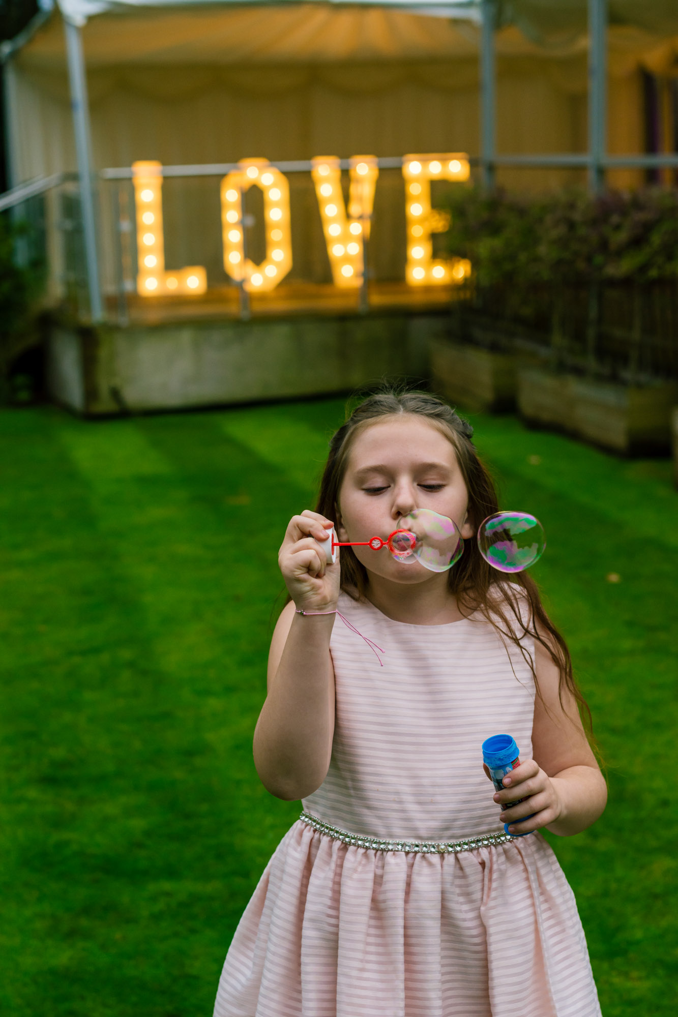 child blowing bubbles at a wedding