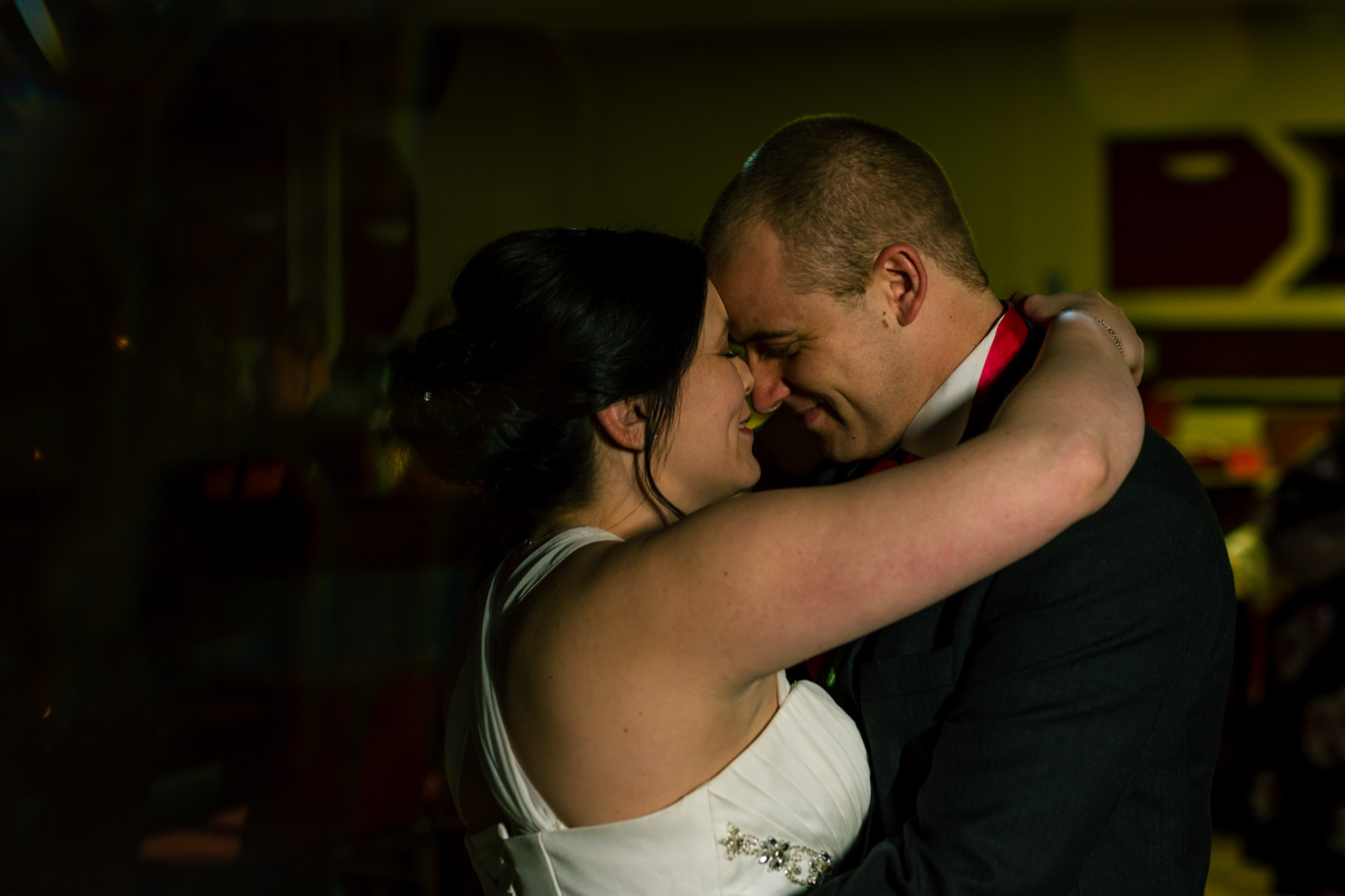 Bride and groom enjoying their first dance. Alone but with everyone around them.