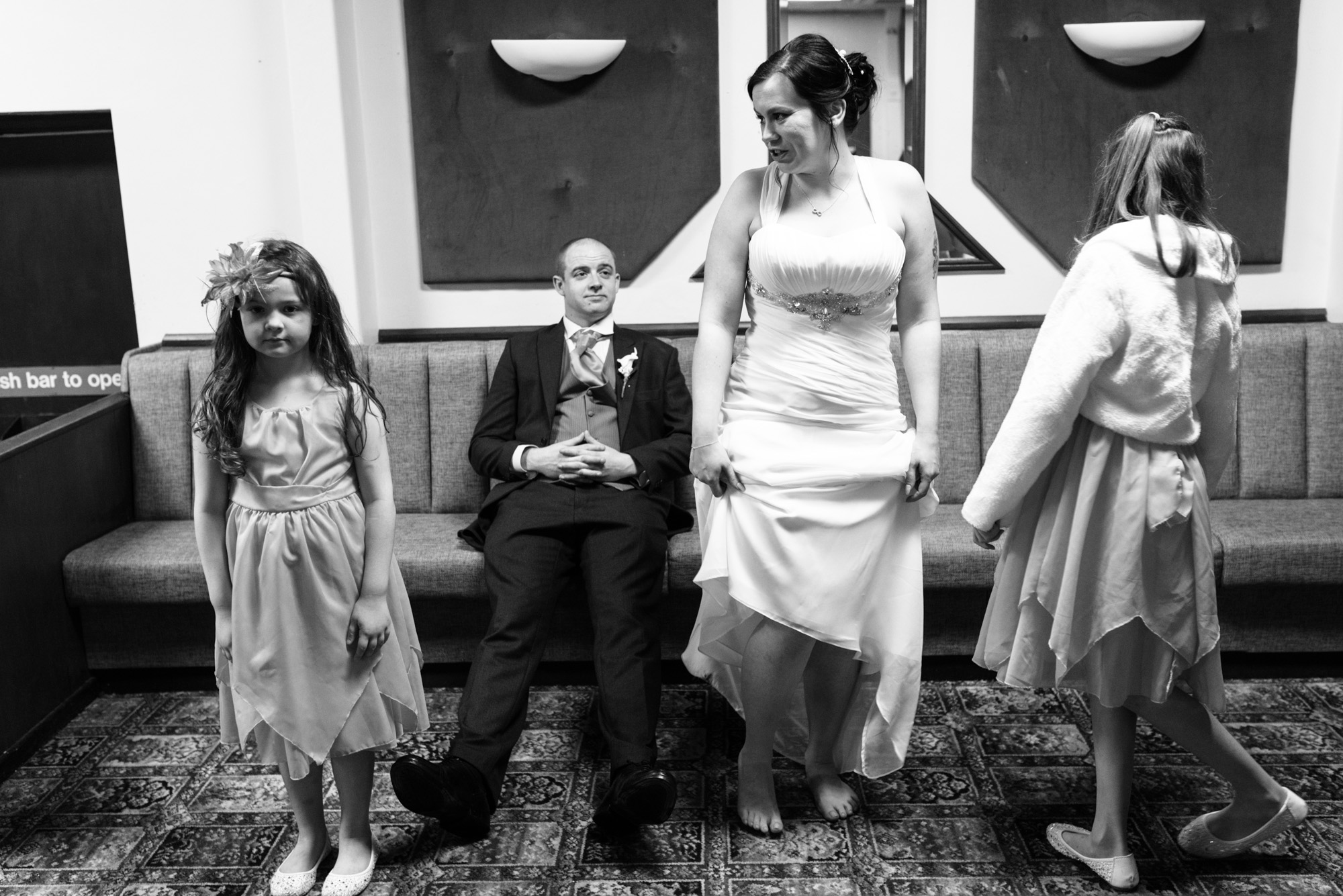 Bride, Groom and two bridesmaids wait for the group shots during the reception.