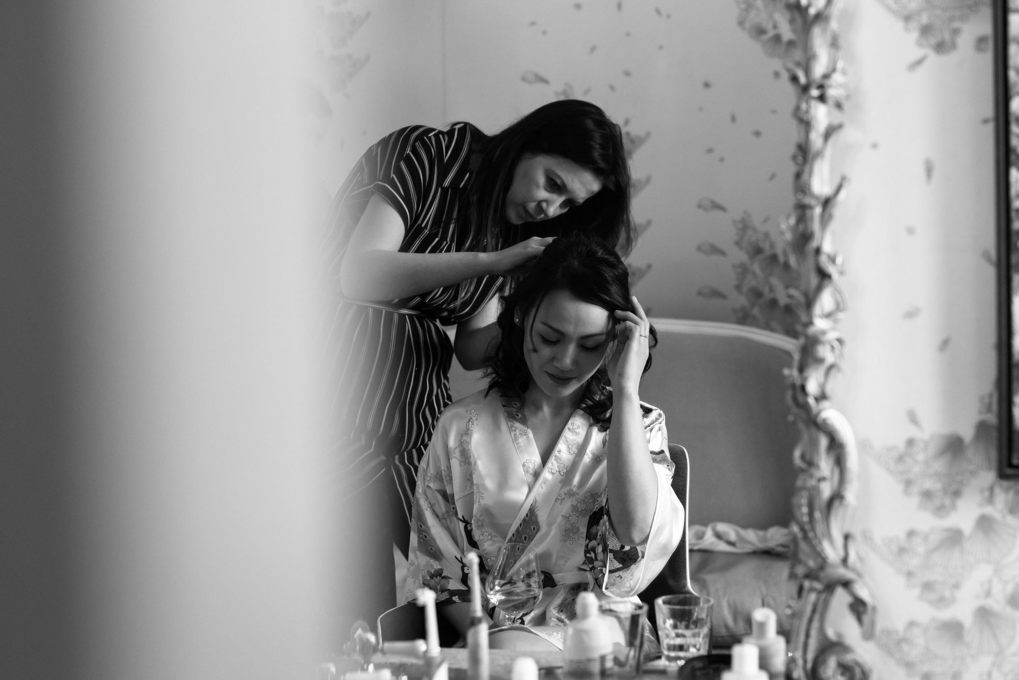 The bridesmaid sits and moves her hair away from her face as she has her hair done ready for the wedding.