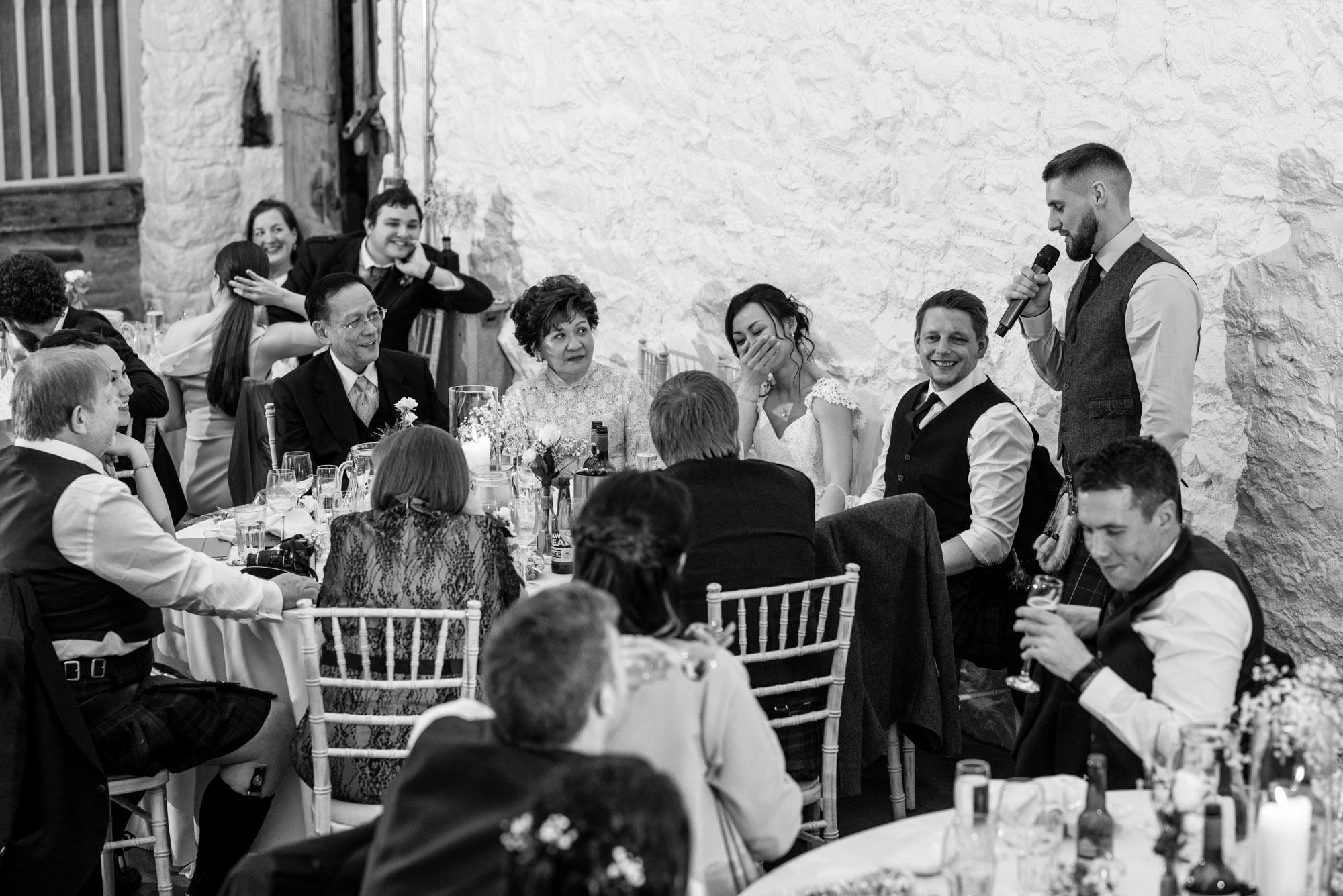 Lots of wedding guests are visible as the best man stands to deliver his speech.