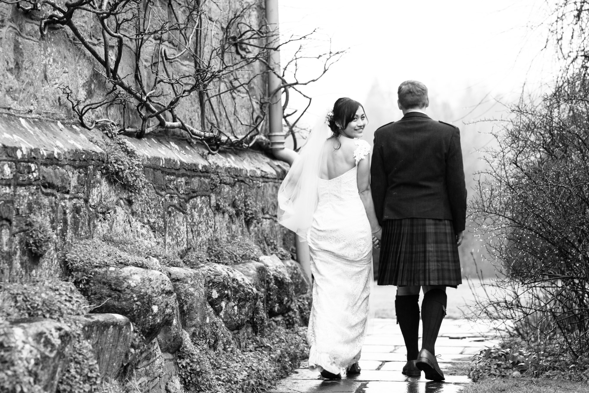 The bride glances round as she walks for her wedding photography at Askham Hall.