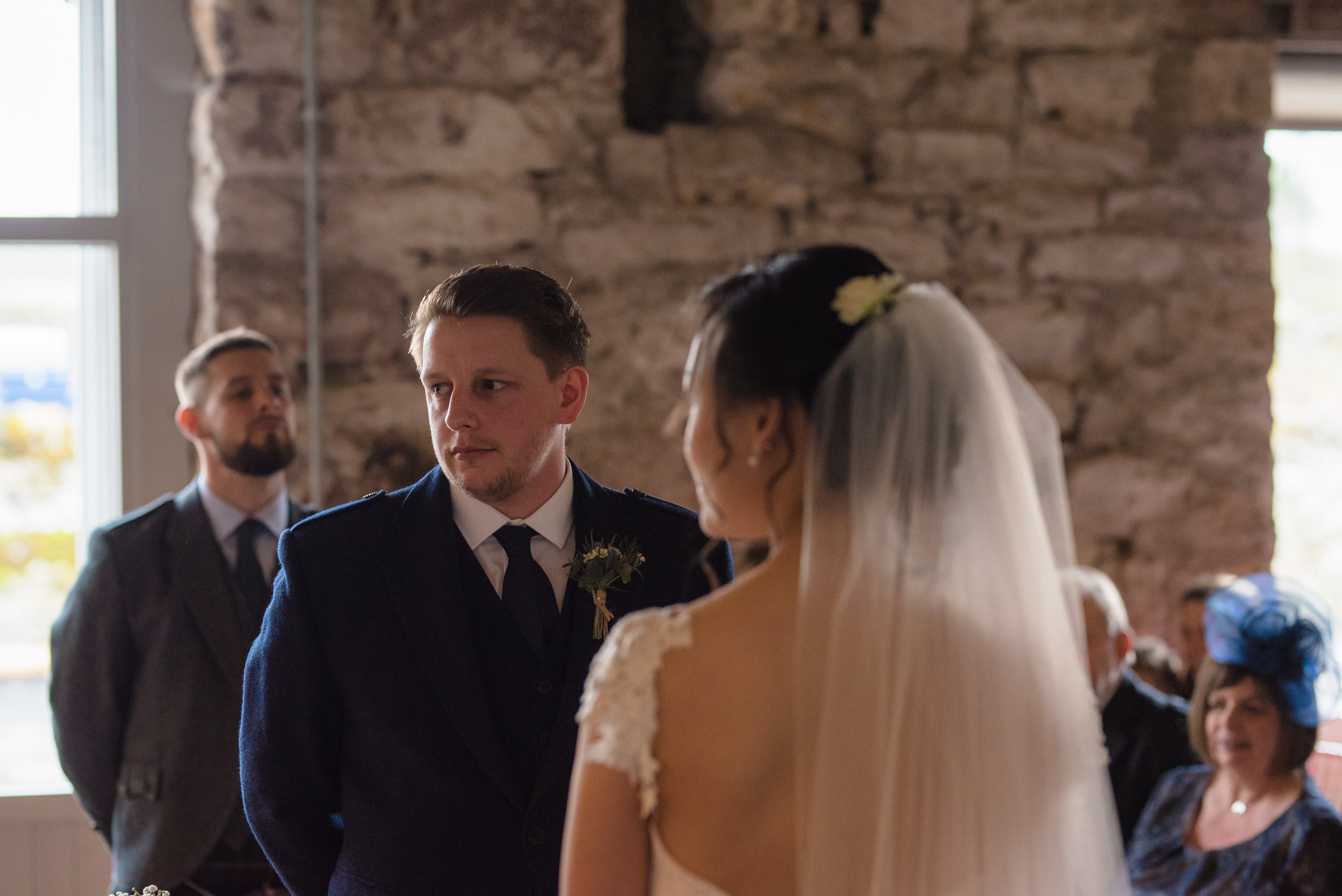 The groom stands in the wedding ceremony and listens intently to the vows.