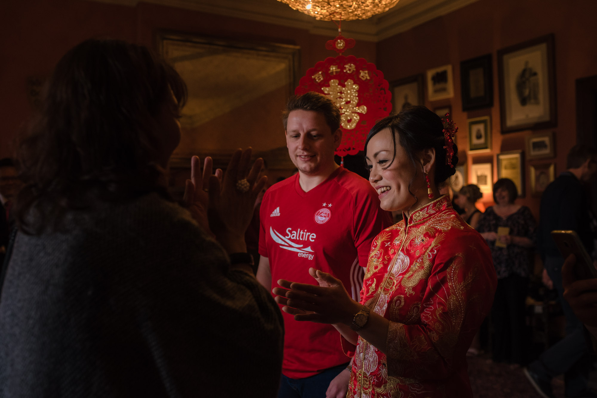 The bride and groom, both dressed in red, smile as they stand in front of their parents during their Chinese tea ceremony.
