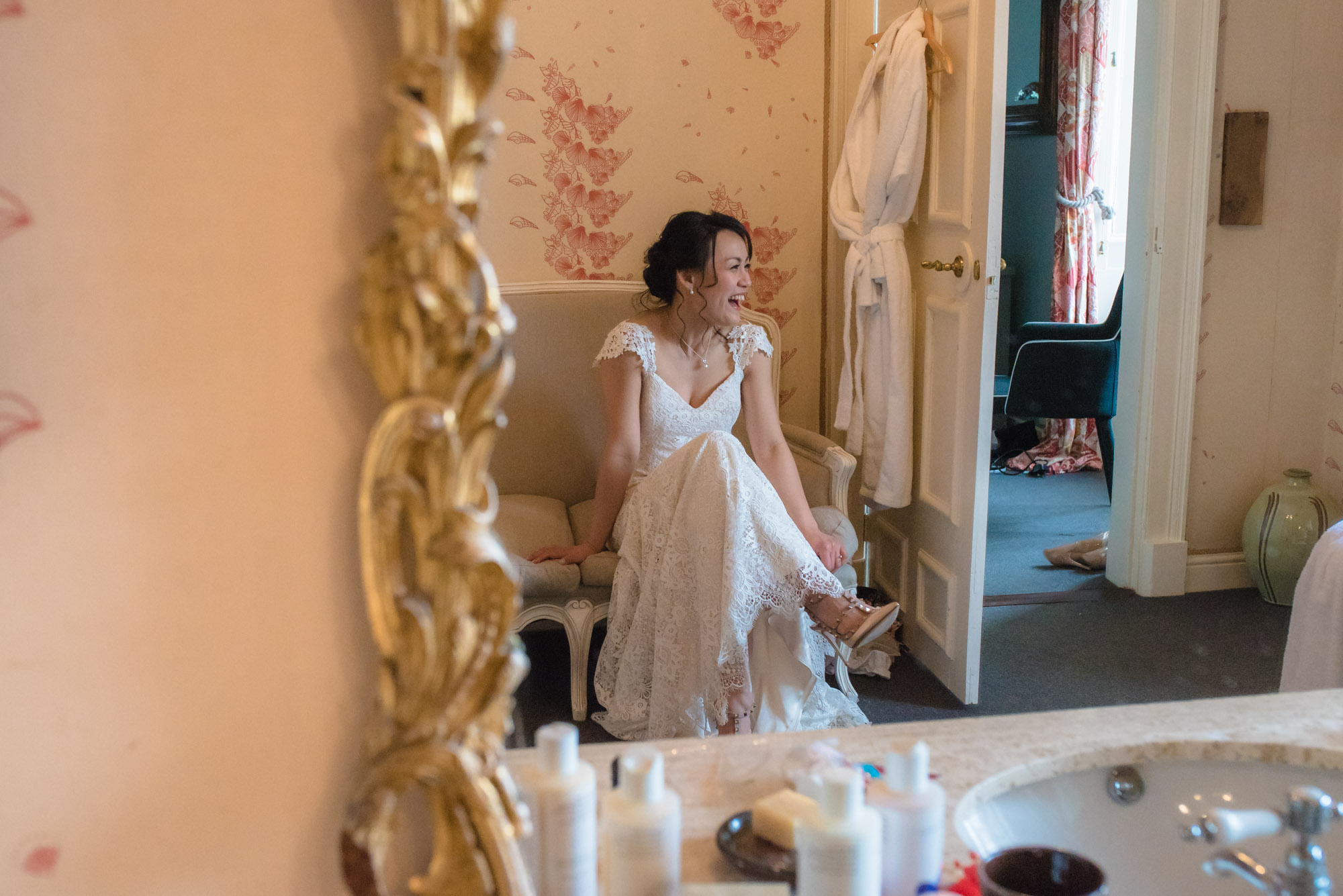 Bride sits on the sofa in the bathroom and waits to be called down to the wedding ceremony.
