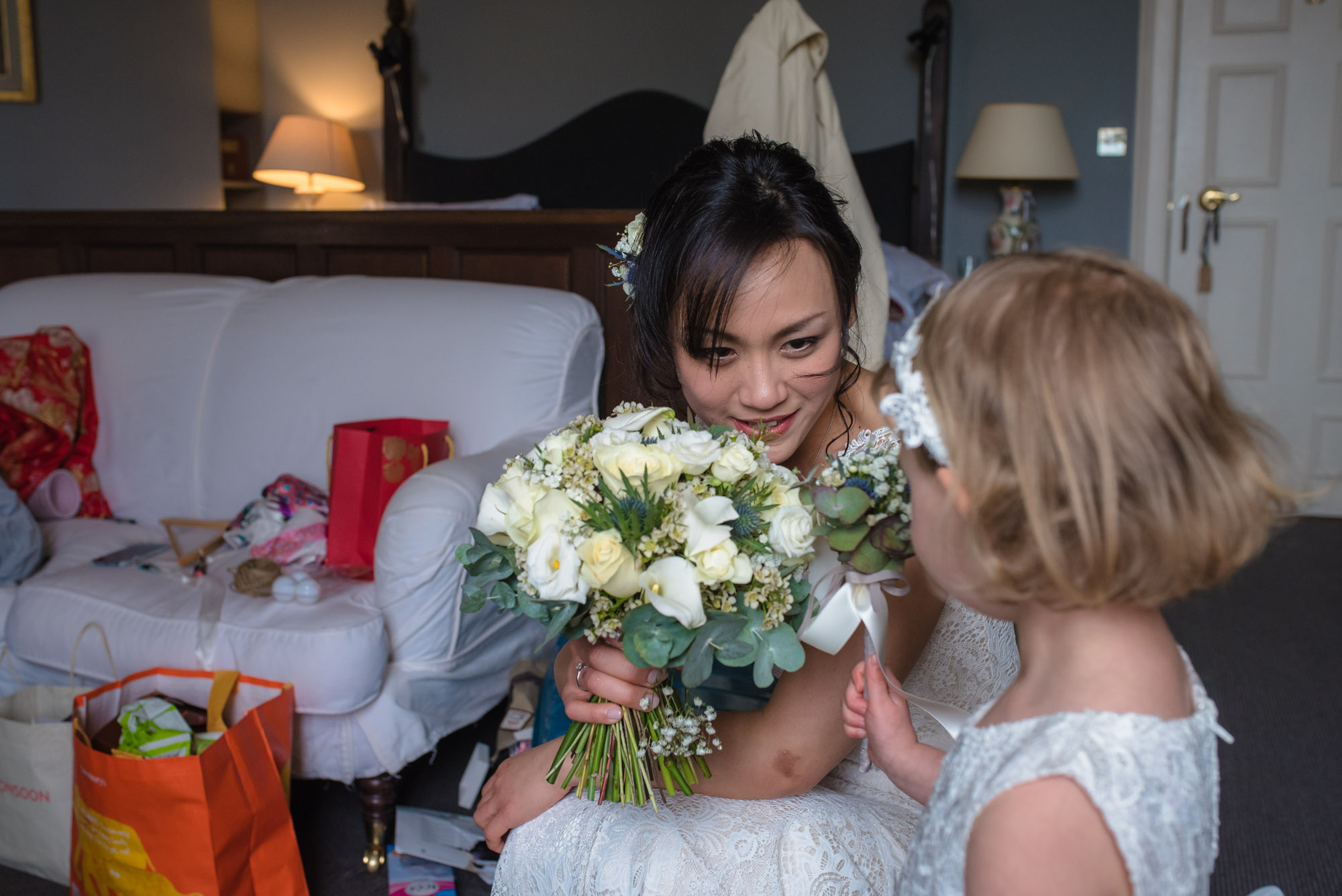 The bride kneels down to show the flower girl her bouquet.