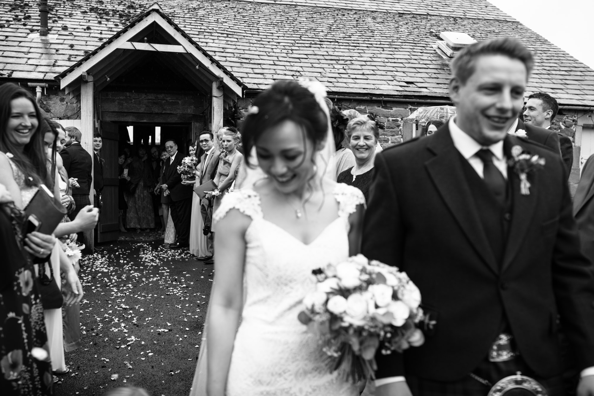 Guests are laughing and smiling at the very end of the confetti shot outside Askham Hall.