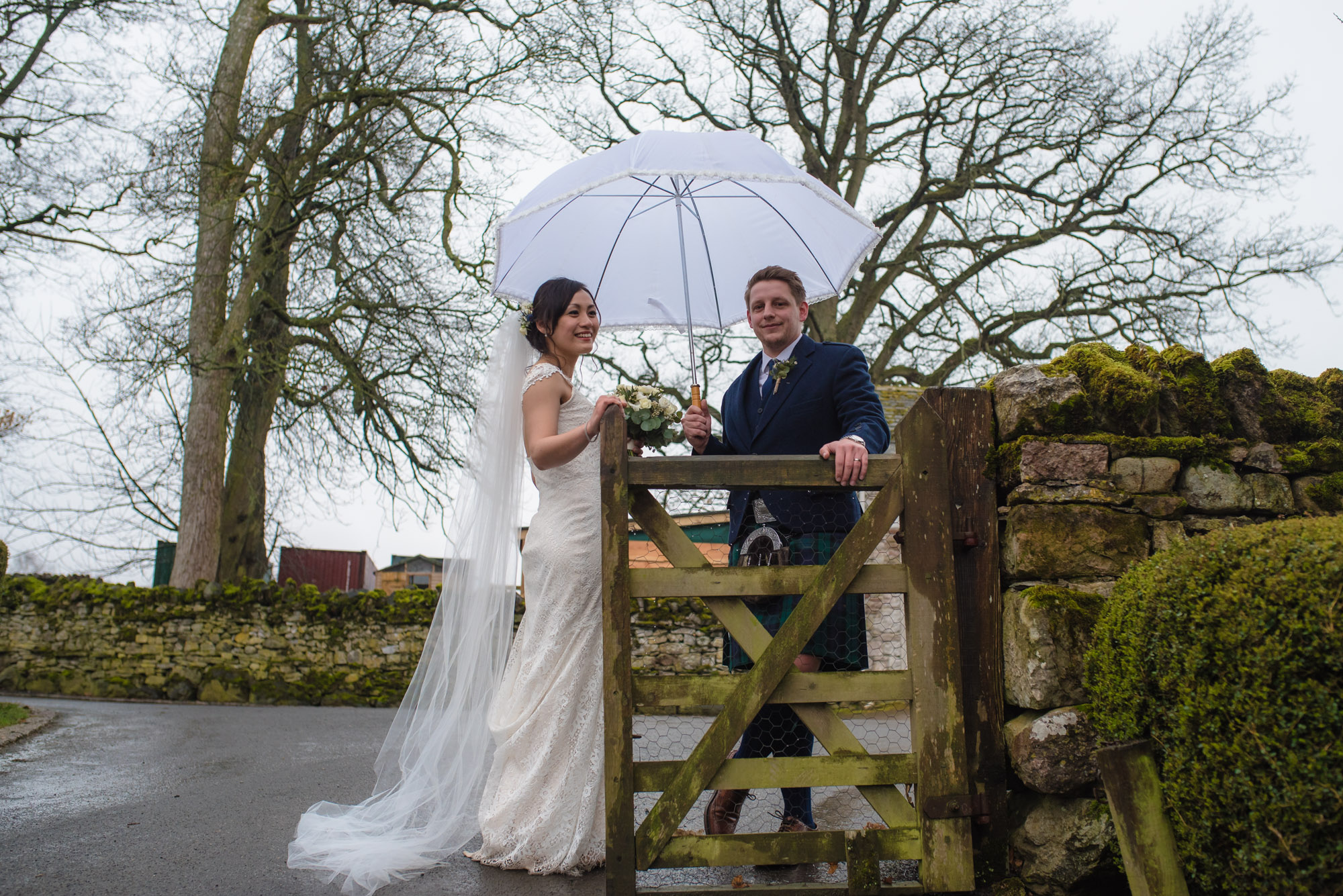 The bride and groom stand by the gate outside the barn at Askham Hall.