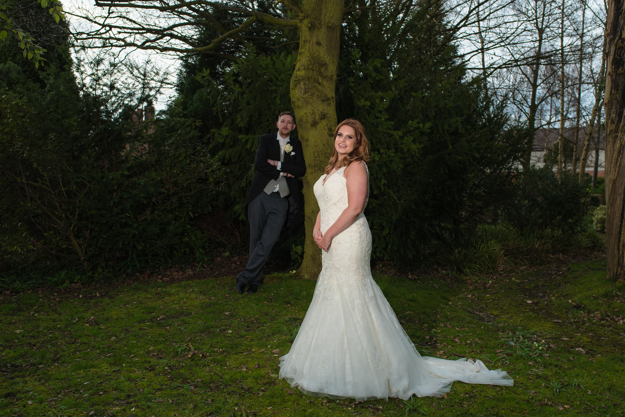 The bride and groom stand by a tree in the grounds of crabwall manor.
