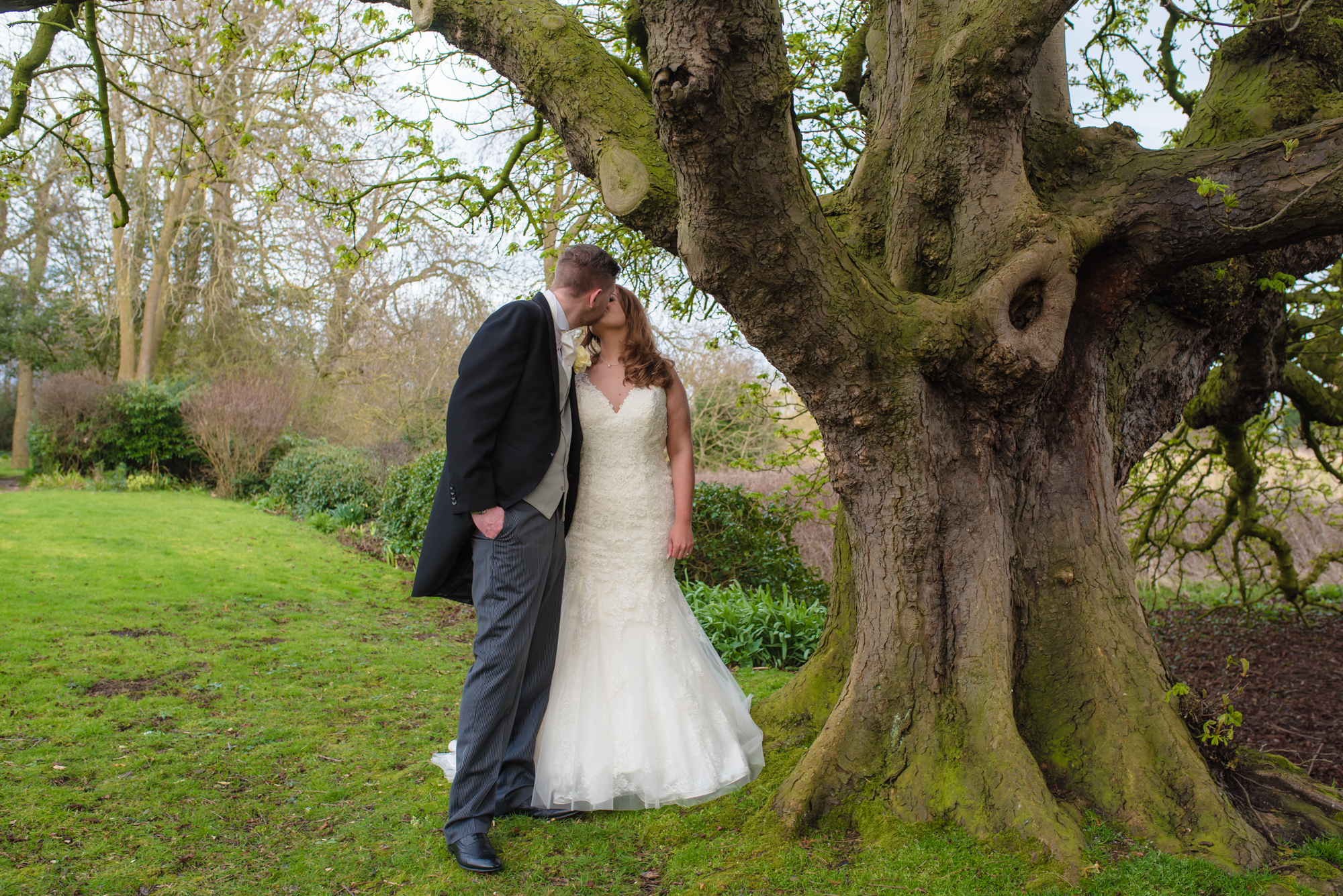Bride and groom share a kiss under a tree at crabwall manor.