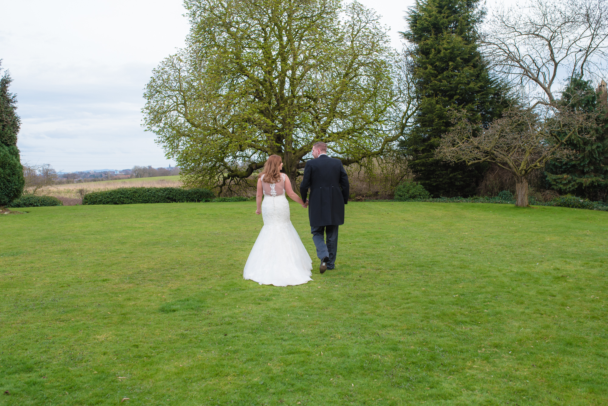 The bride and groom walking away from their wedding venue towards fields in the distance.