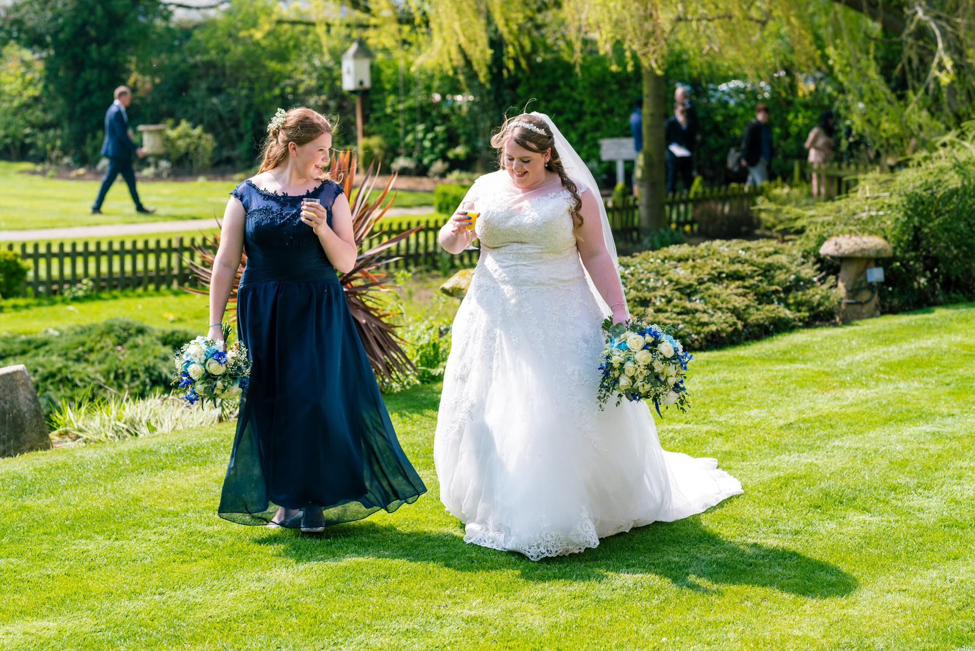 Bride and bridesmaid walk across the lawn