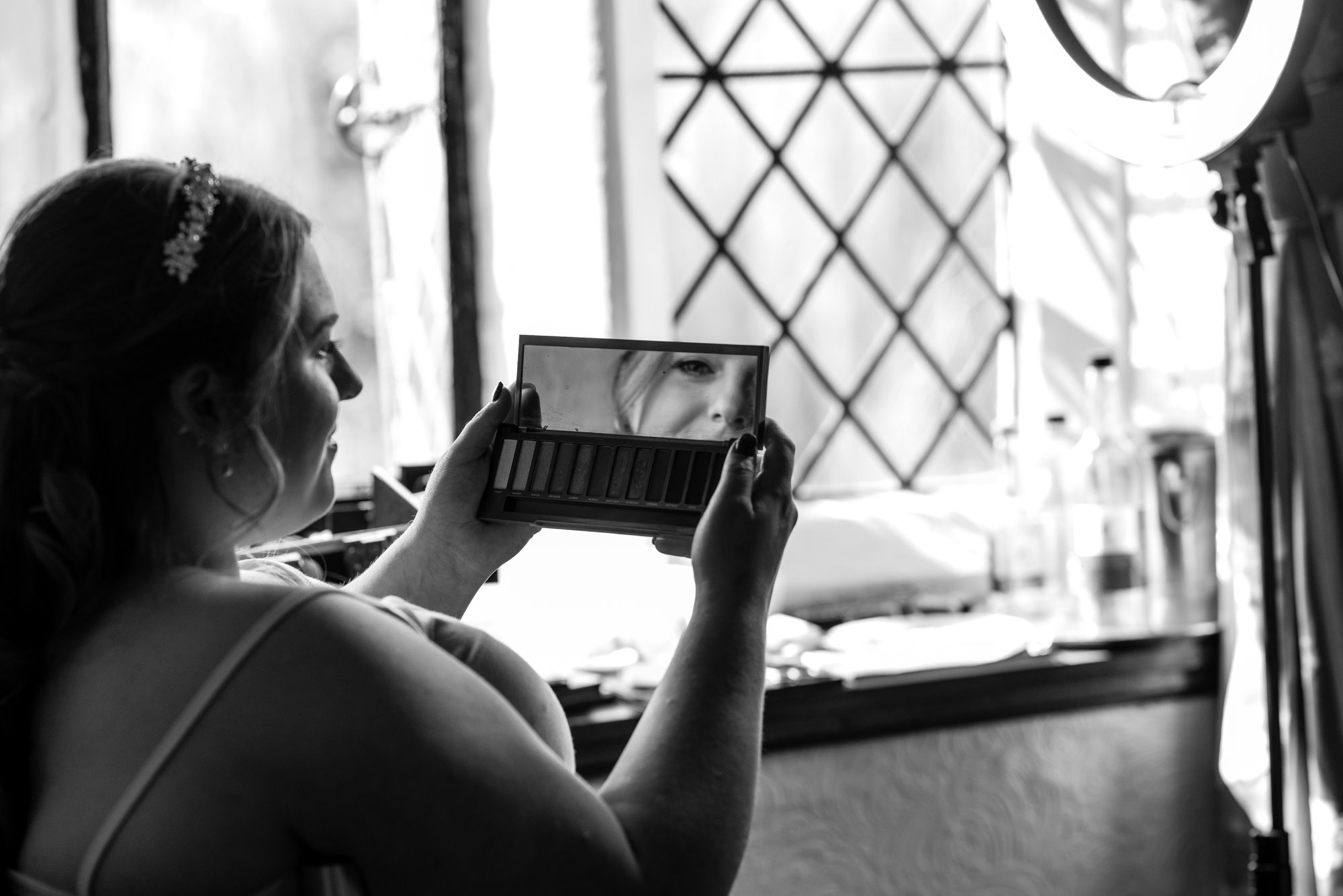 Bride checking her make-up in a mirror