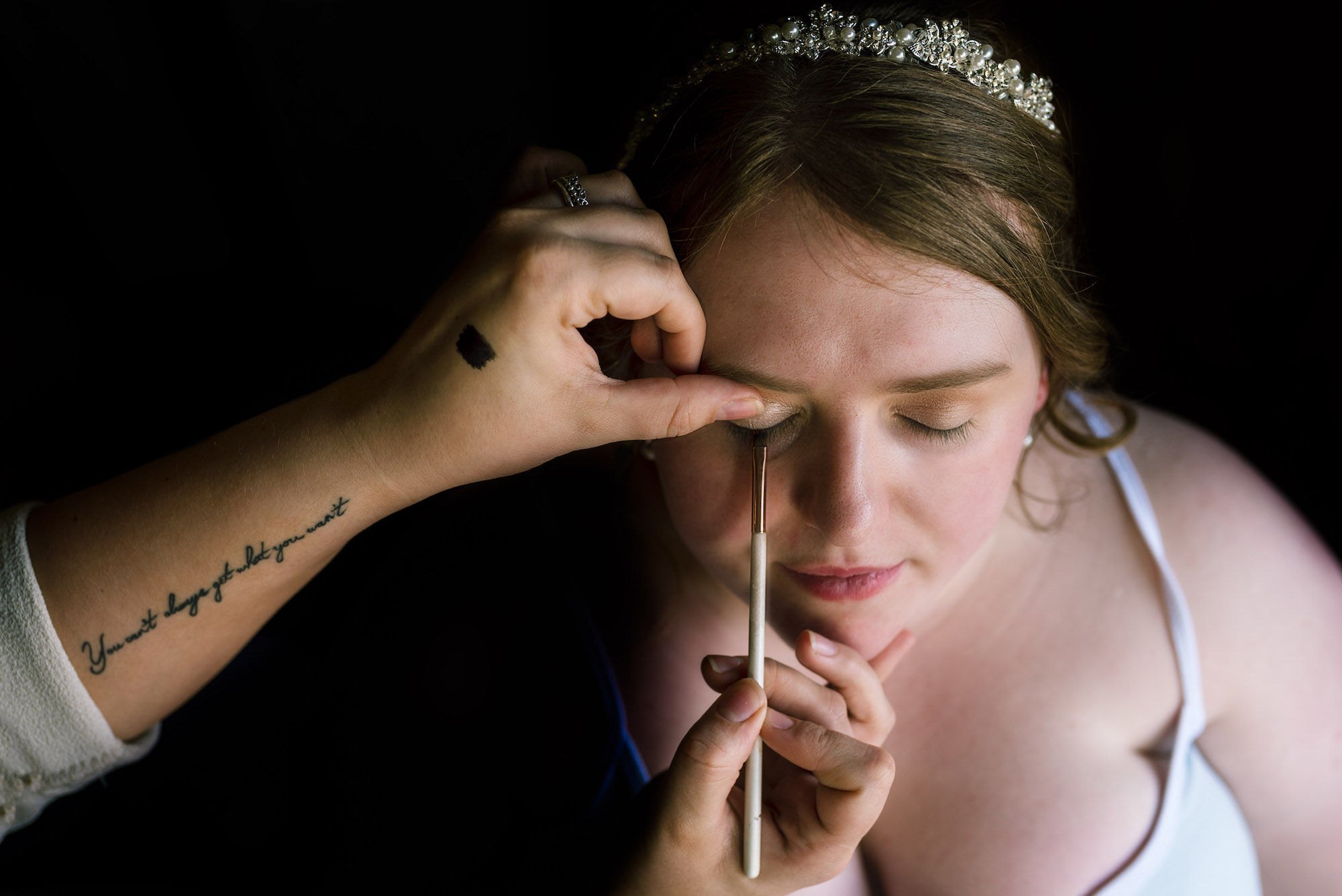 Downwards shot towards the bride having her eyeshadow applied