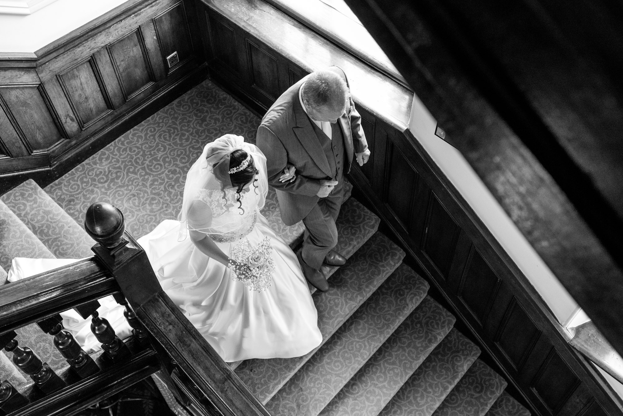 Father of the bride leads his daughter down the stairs