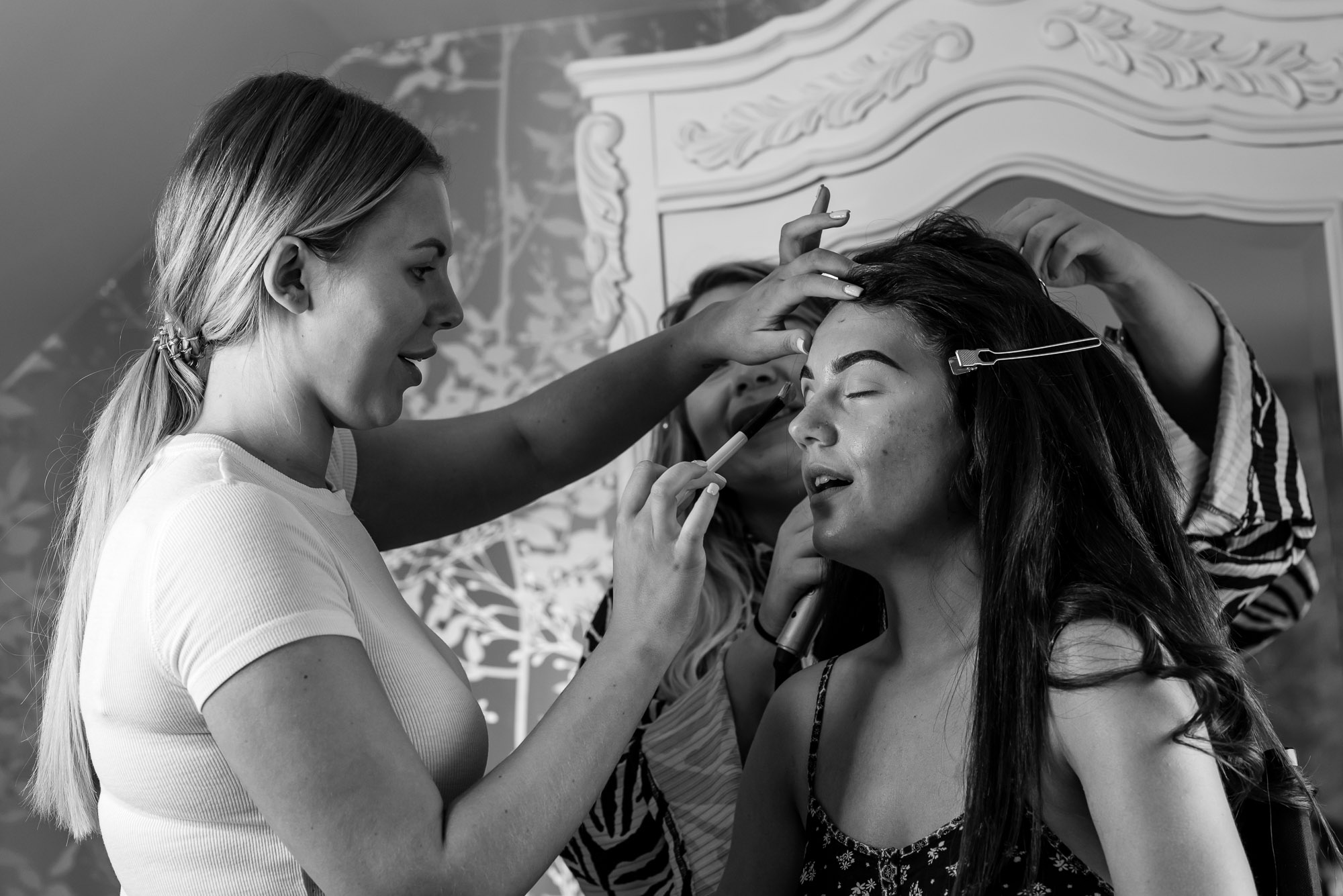 The bride having her eye makeup done during the wedding preparations