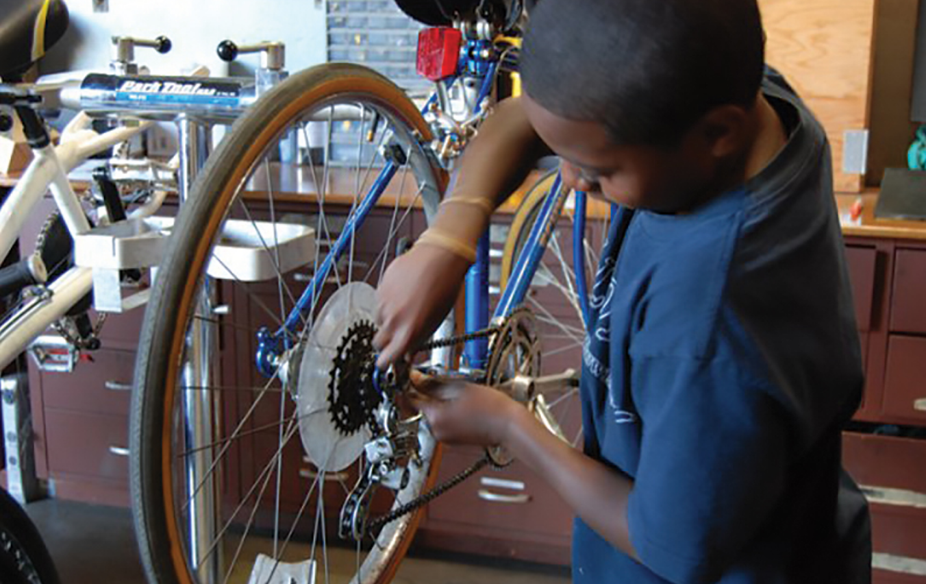 Neighborhood youth earn bikes to to take as their own through participation in the Earn-a-Bike program. Once they know what they're doing they return to staff community bike fix-a-thons, offering free bike repairs to neighbors.